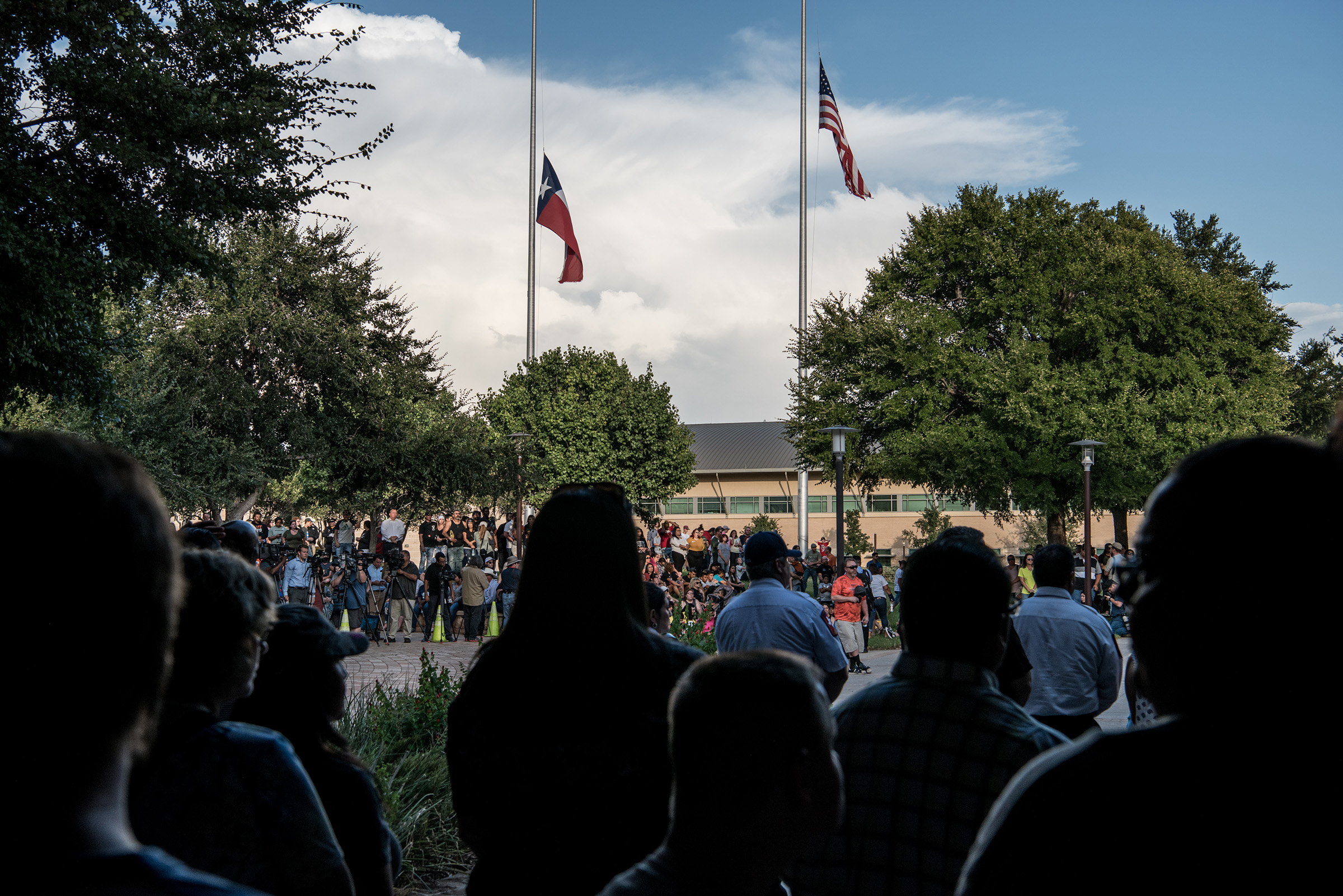 Flags fly at half mast over a prayer vigil at the University of Texas of the Permian Basin for the victims of a mass shooting in Odessa, TX, on Sept. 1, 2019.