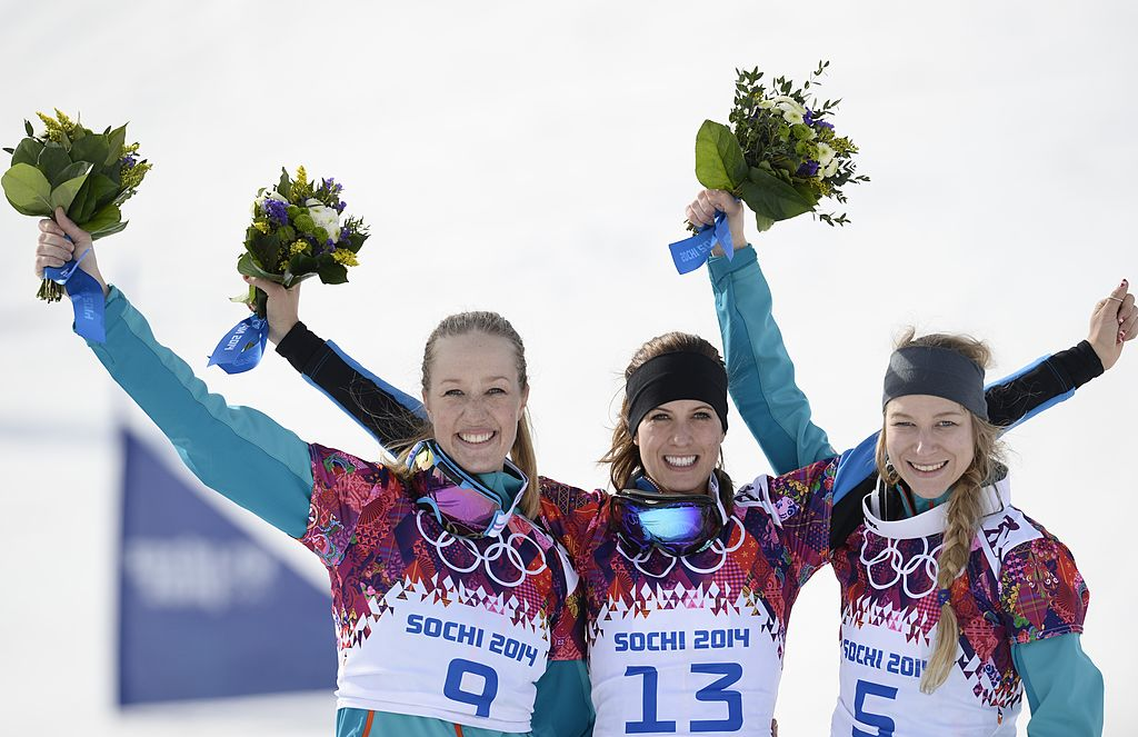 Silver Medallist, Germany's Anke Karstens; Gold Medallist, Austria's Julia Dujmovits; and Bronze Medallist, Germany's Amelie Kober celebrate at the Women's Snowboard Parallel Slalom Flower Ceremony at the Rosa Khutor Extreme Park during the Sochi Winter Olympics on February 22, 2014.