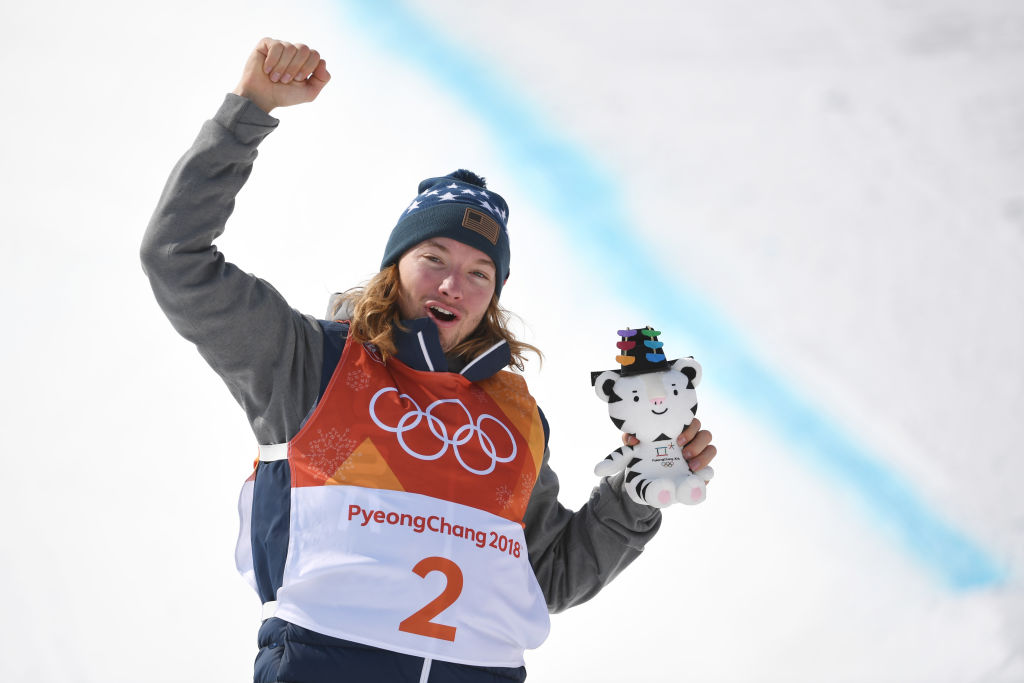 David Wise from the USA celebrates winning the gold medal on the podium during the flower ceremony.