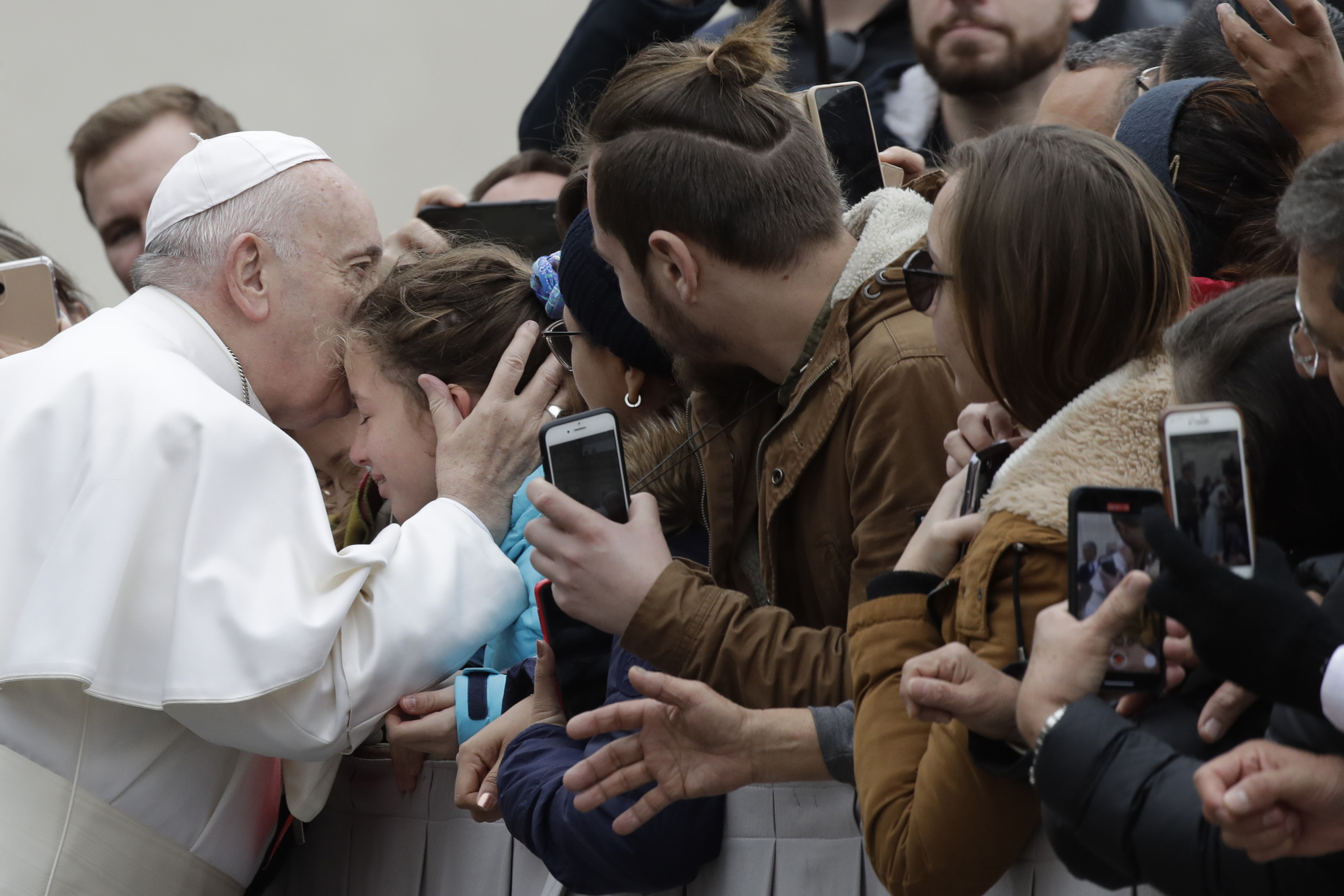 Pope Francis kisses a child in St. Peter's Square at the Vatican before leaving after his weekly general audience, on Feb. 26, 2020.