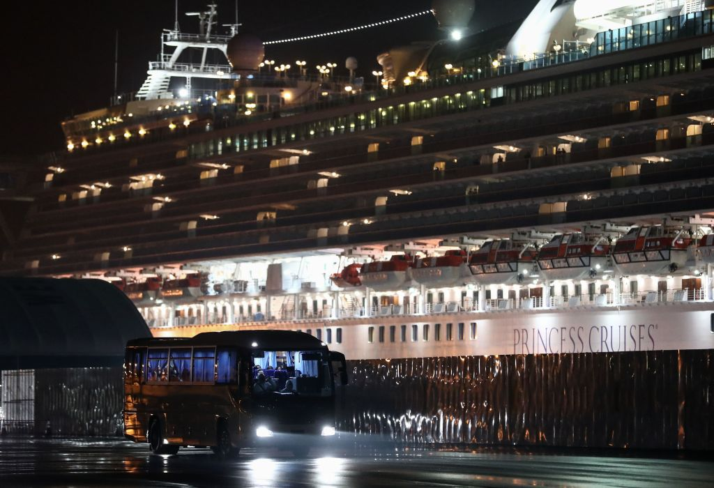 A bus carrying American citizens leaves the Daikaku Pier Cruise Terminal in Yokohama port, next to the Diamond Princess cruise ship in Japan on Feb. 17, 2020.