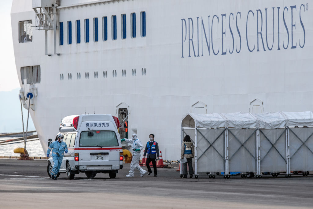 Medical staff in protective clothing load coronavirus patients from the Diamond Princess cruise onto an ambulance in Yokohama, Japan, on Feb. 7, 2020.
