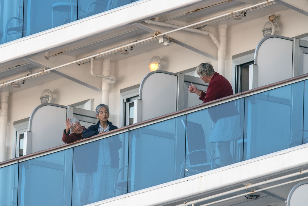 A woman gives a thumbs up to fellow passengers as they stand on their cabin balconies of the quarantined Diamond Princess cruise ship in Yokohama, Japan., on Feb. 11, 2020.