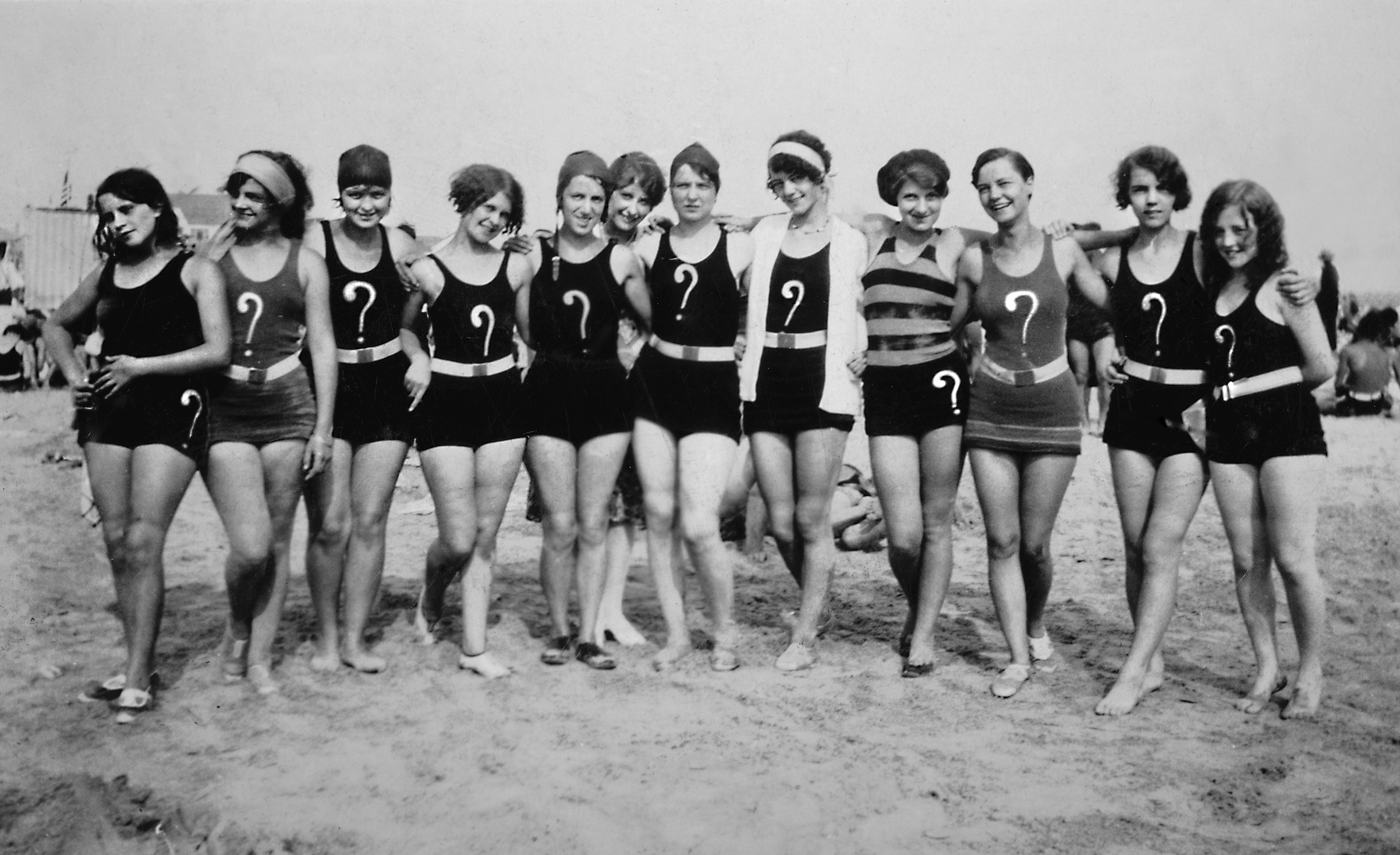 A group of flappers with question marks on their swim suits pose together on the beach, ca. 1925.