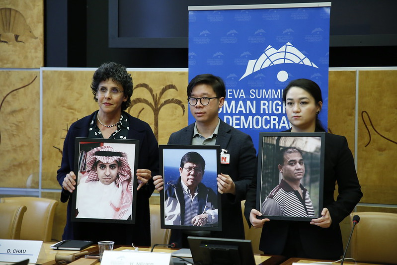 Ellham Manea (L) holds a photo of political prisoner Raif Badawi.