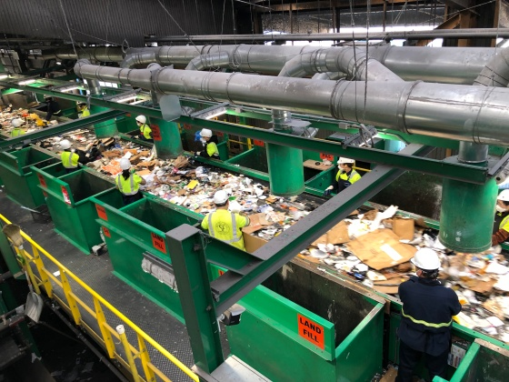 Workers sort through mixed recycling in a Recology plant in San Francisco