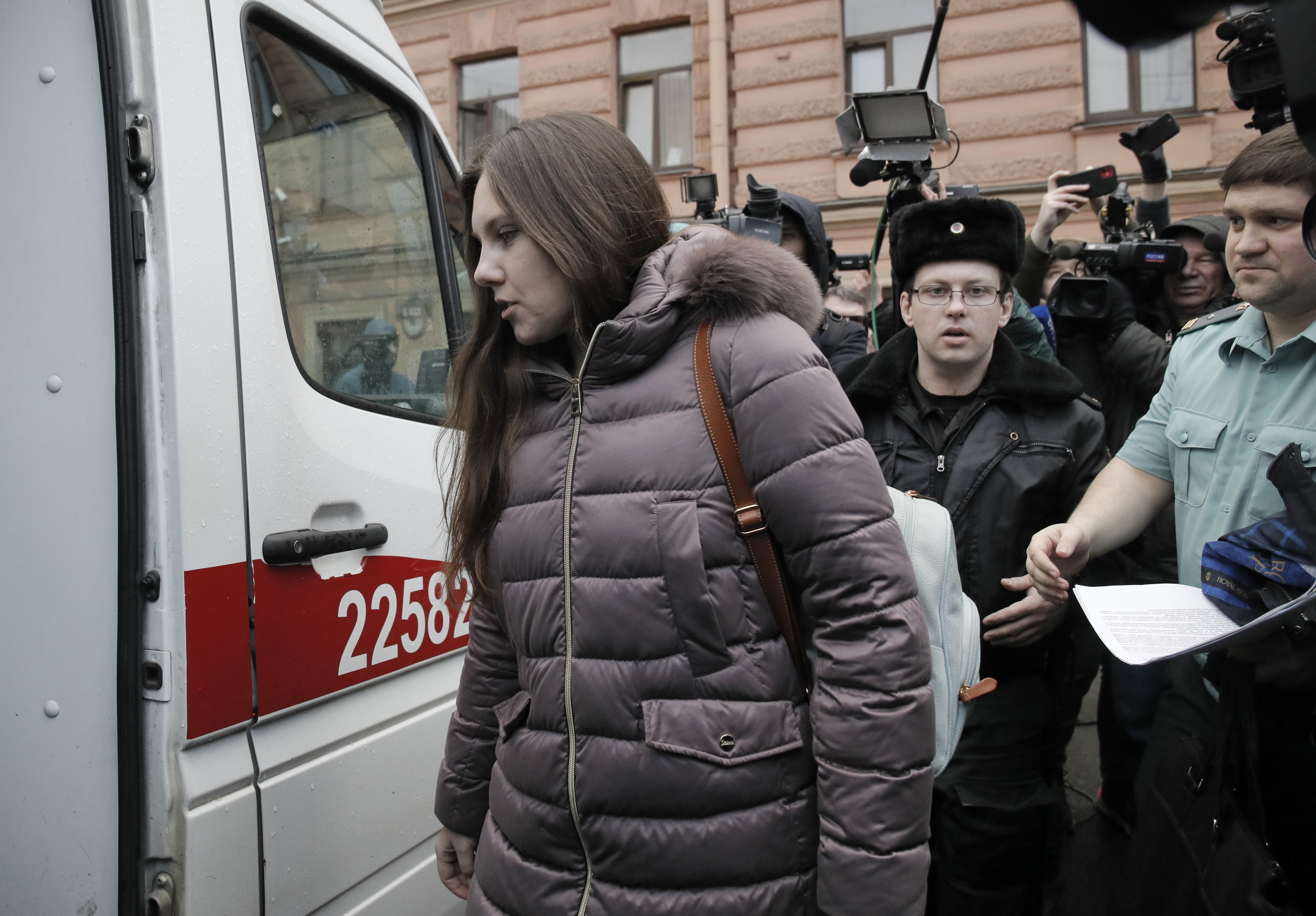 Alla Ilyina, who broke out of the hospital on Feb. 7 after learning that she would have to spend 14 days in isolation instead of the 24 hours doctors promised her, is escorted by a bailiffs form a court after a session in St. Petersburg, Russia, on Feb. 17, 2020.