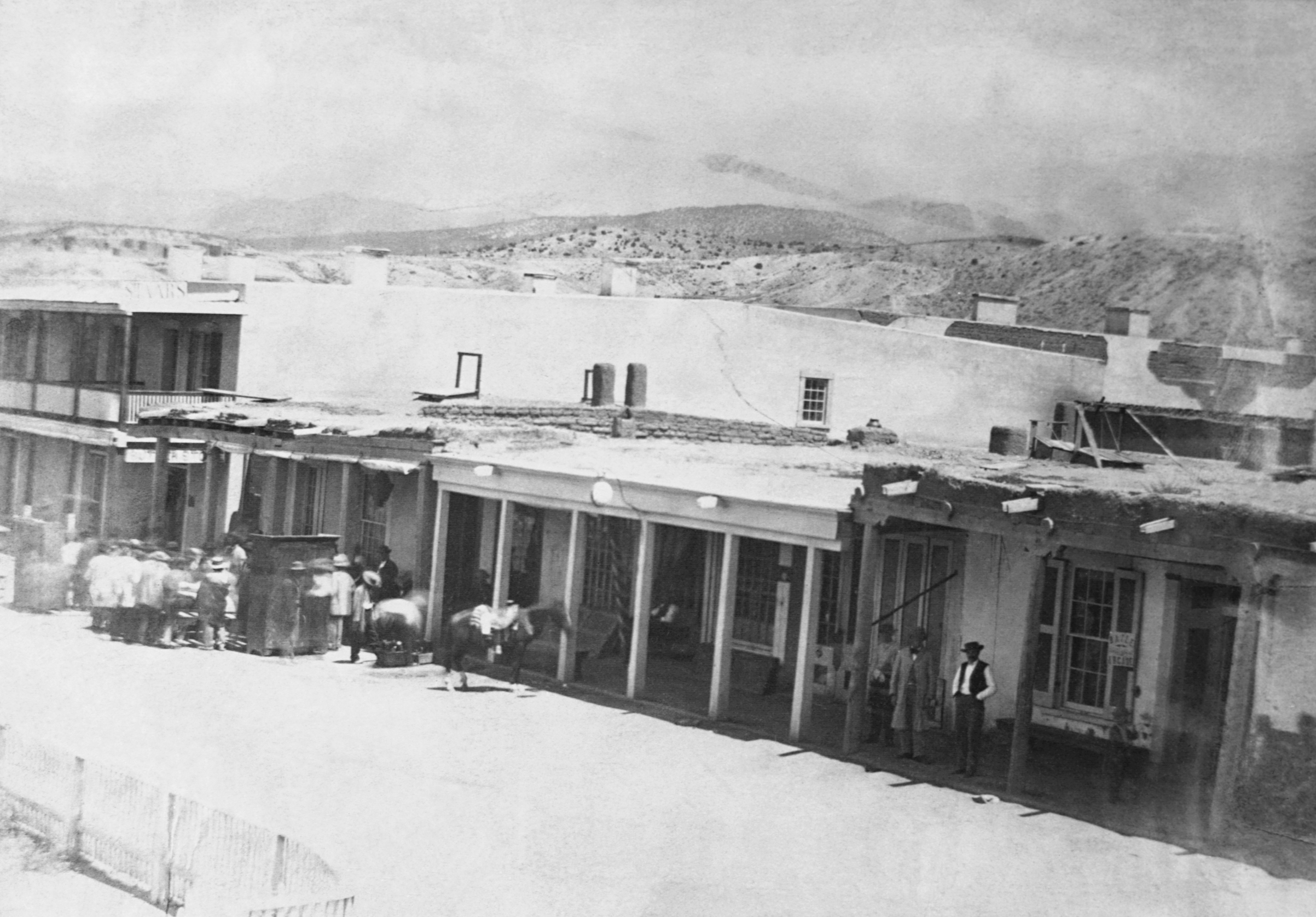 People stand on the sidewalk and in the street at the east side of Plaza in Santa Fe, N.M., 1866.