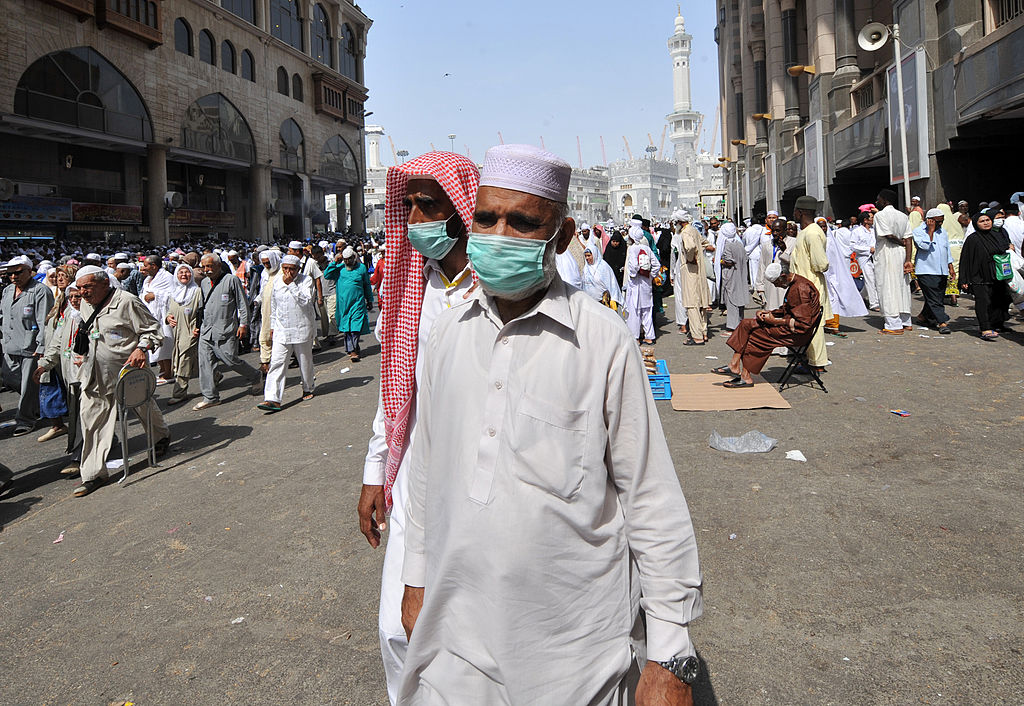 Muslim pilgrims wearing a mask leave after the Friday prayer at Mecca's Grand Mosque, on Oct. 11, 2013 as hundreds of thousands of Muslims have poured into the holy city of Mecca for the annual hajj pilgrimage.