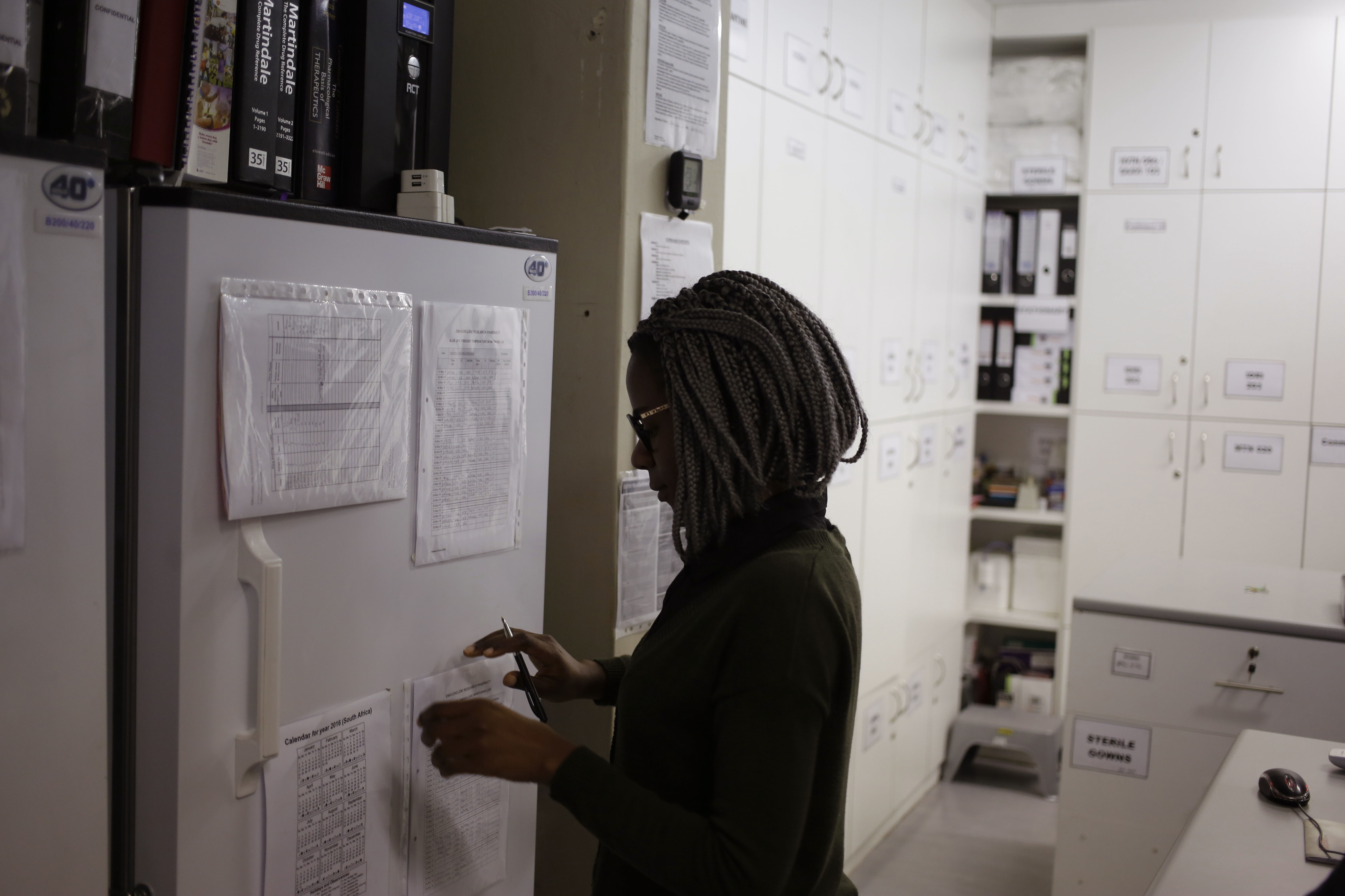 In a Nov. 30, 2016 file photo, pharmacist Mary Chindanyika looks at documents on a fridge containing a trial vaccine against HIV on the outskirts of Cape Town, South Africa. The latest attempt at an HIV vaccine has failed.