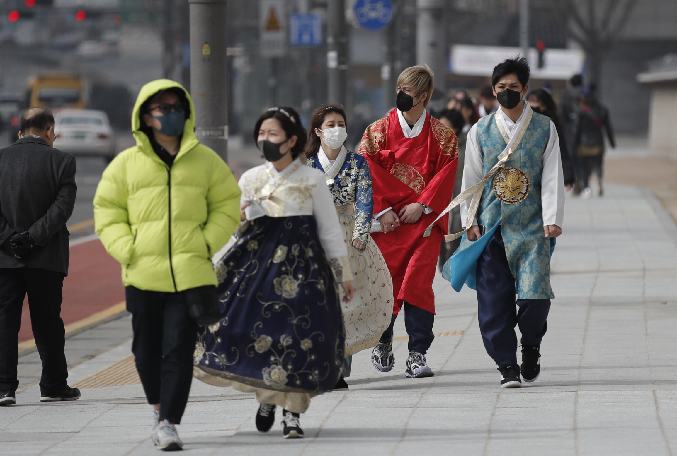 Visitors wearing face masks walk near the Gwanghwamun, the main gate of the 14th-century Gyeongbok Palace, and one of South Korea's well-known landmarks, in Seoul, South Korea, on Feb. 22, 2020.