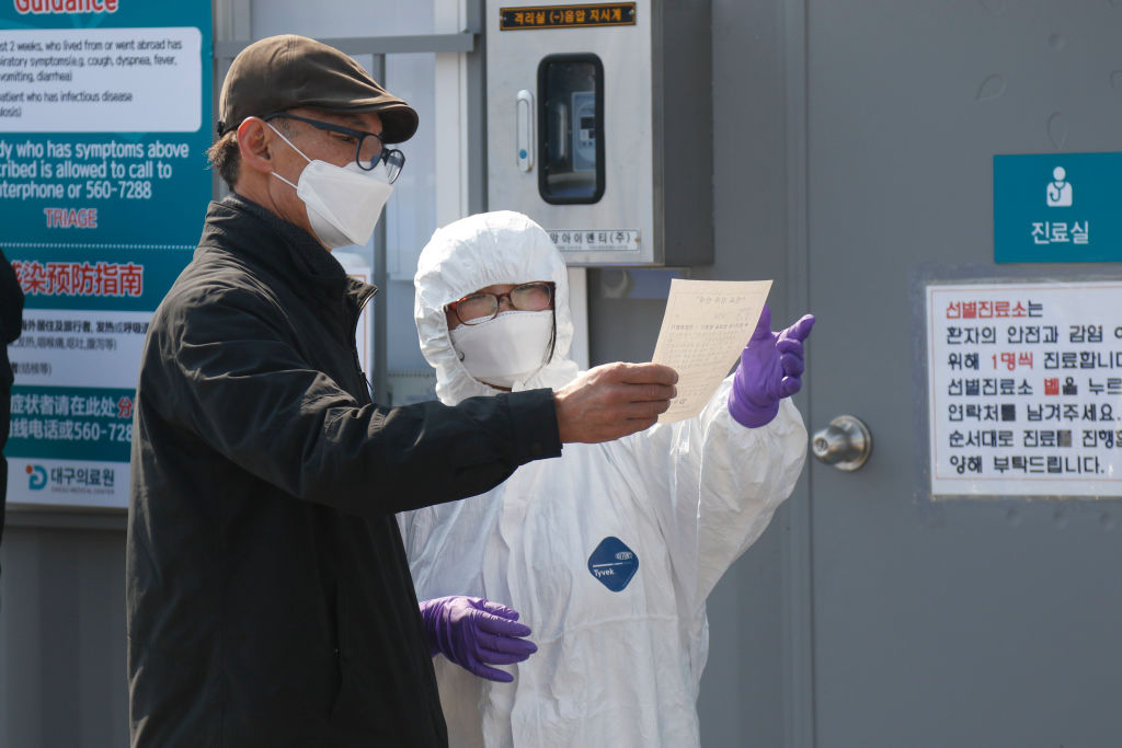 Staff at a hospital in the southeastern city of Daegu, South Korea, where new cases of the virus have been linked to a mysterious religious sect