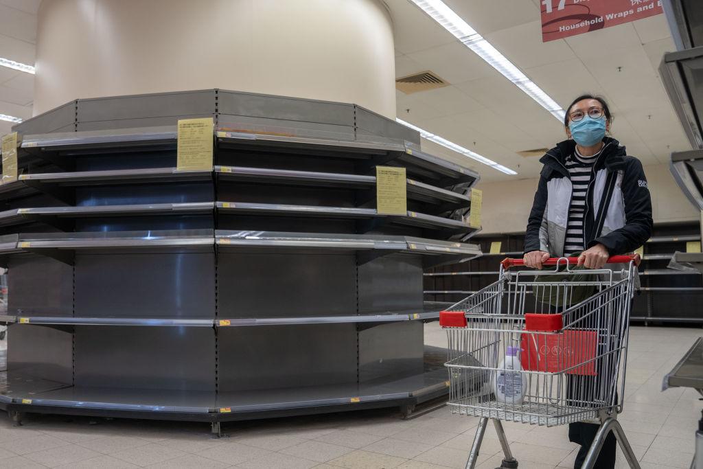 A shopper walks past empty supermarket shelves in Hong Kong on Feb. 12, 2020.