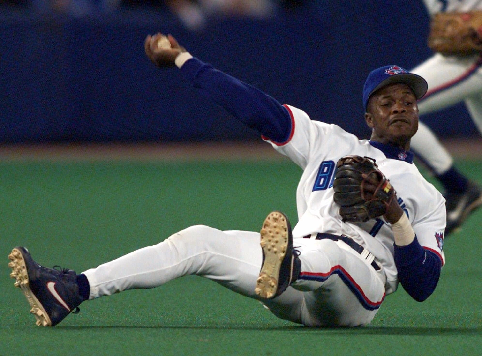 Toronto Blue Jays third baseman Tony Fernandez throws to first as he tumbles to the turf during third-inning AL action against the Chicago White Sox in Toronto, on Sept. 17, 1999.
