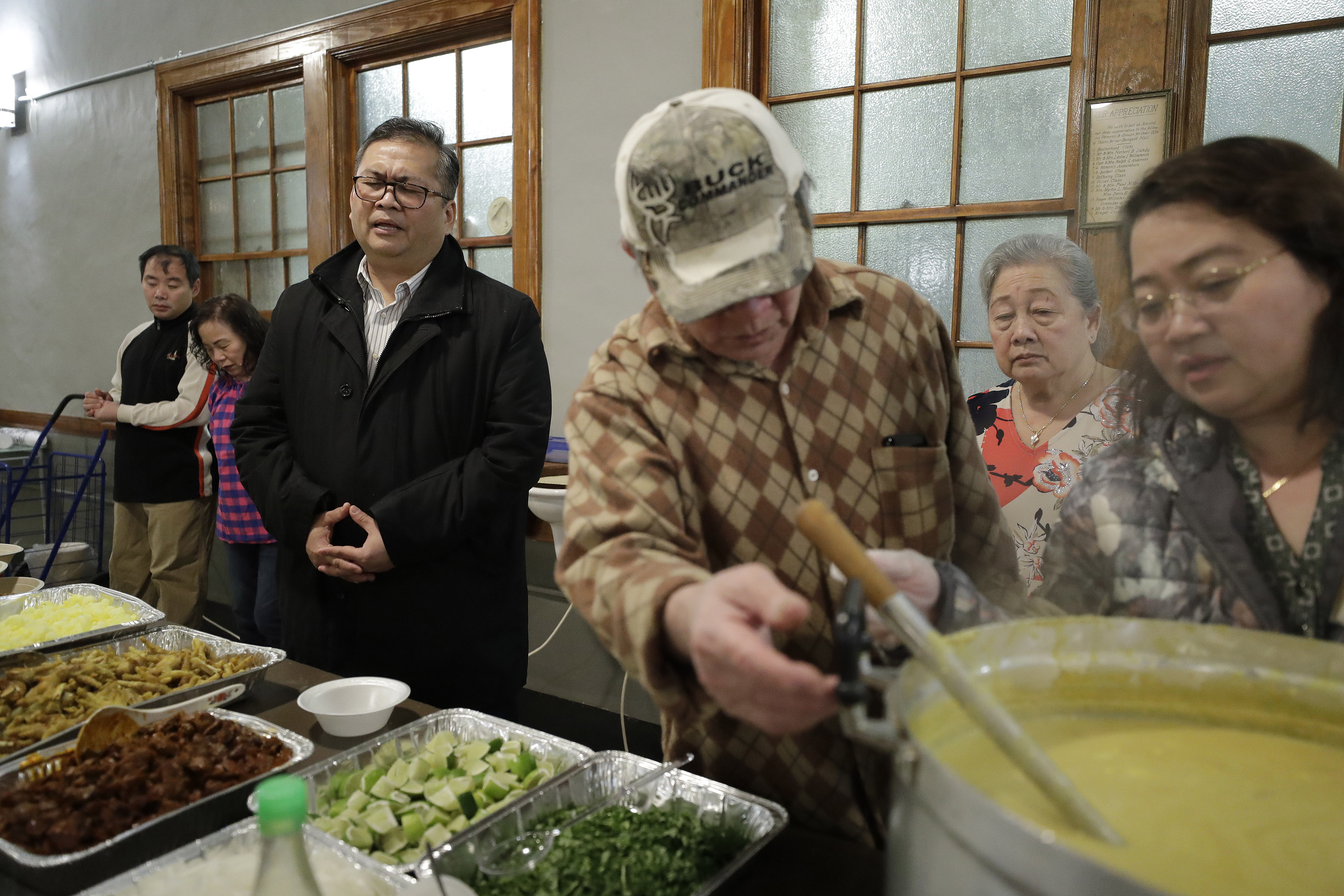 Baptist Pastor Clifford Maung, third from left, recites a prayer as Chin Sai, center, and Myint Myint Swe, right, prepare food following services at the Overseas Burmese Christian Fellowship in Boston on Feb. 16, 2020.
