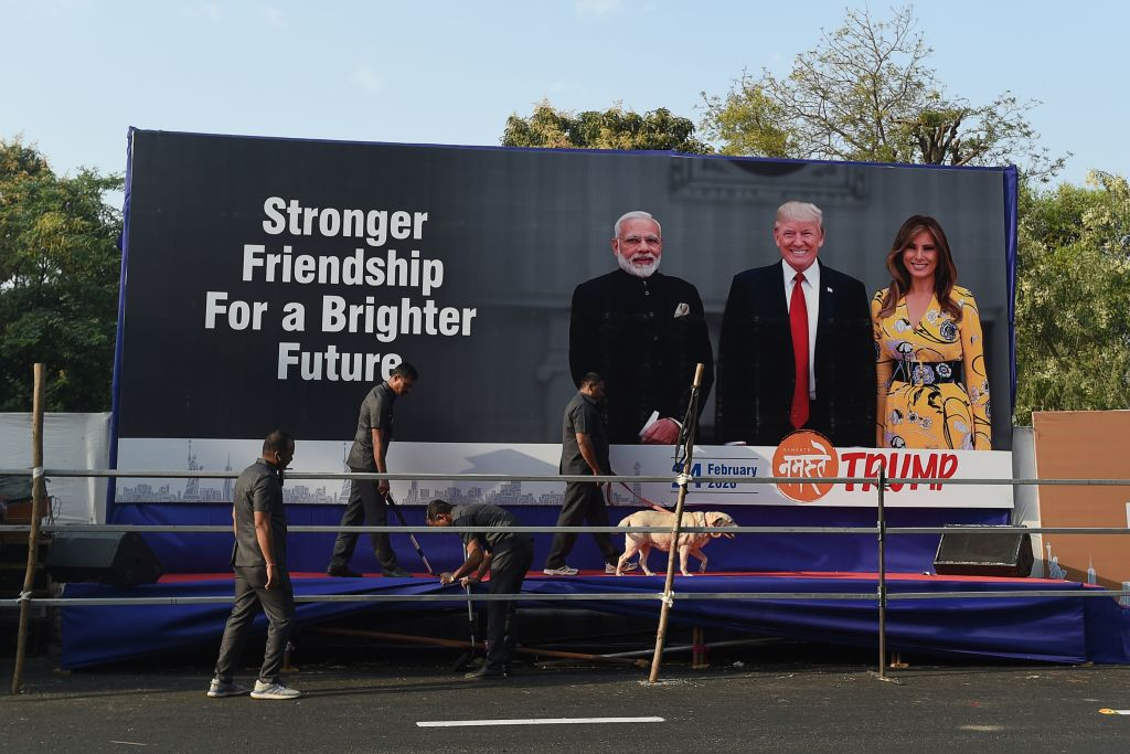 Gujarat police's bomb detection disposal squad officials, along with a sniffer dog, inspect a stage displaying pictures of India's Prime Minister Narendra Modi (L), U.S. President Donald Trump (C) and First Lady Melania Trump (R), on the outskirts of Ahmedabad on February 23, 2020, ahead of Trump's visit to India.