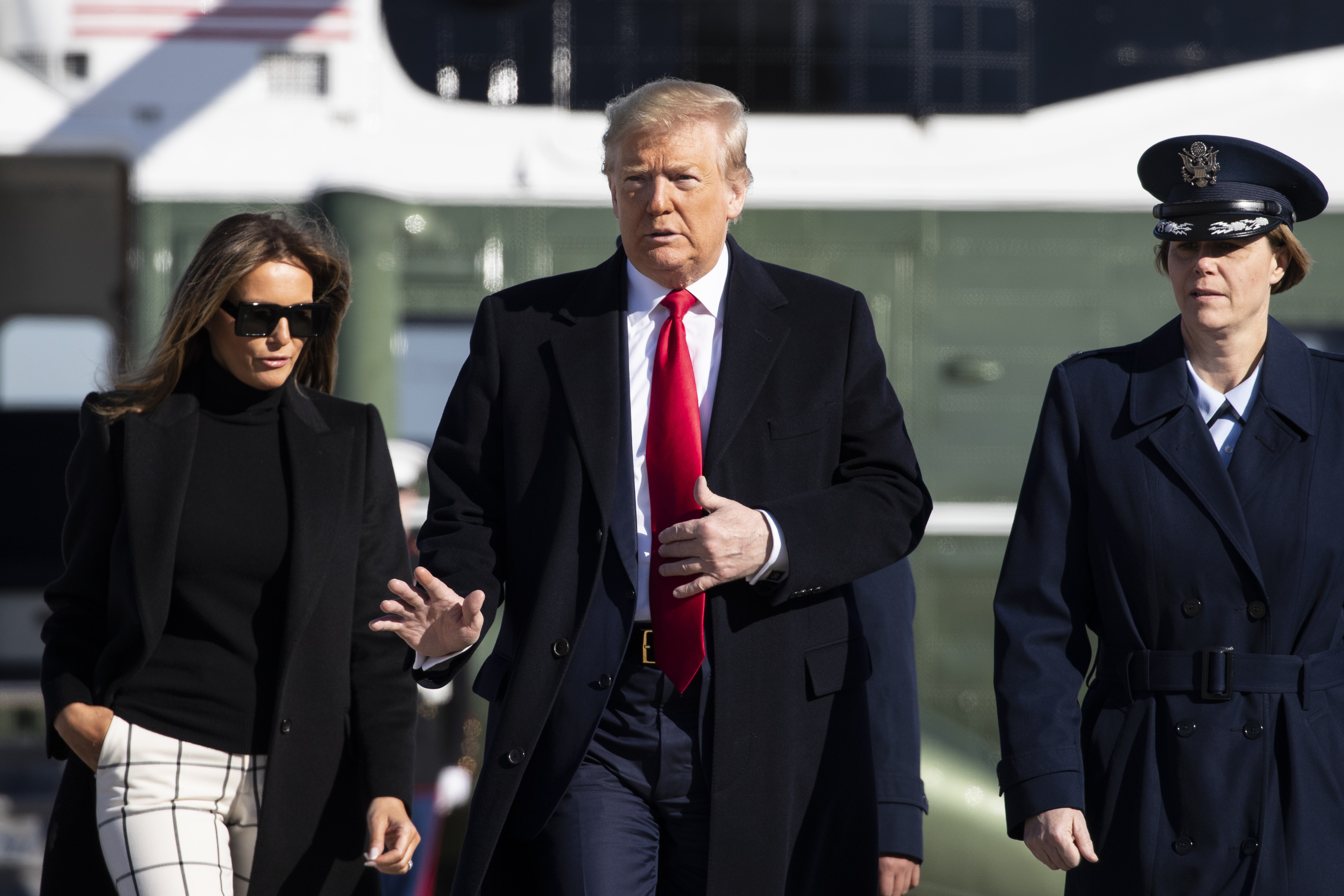 President Donald Trump, with first lady Melania Trump, wave as they walk across the tarmac to board Air Force One during their departure, on Feb. 23, 2020, at Andrews Air Force Base, Md.