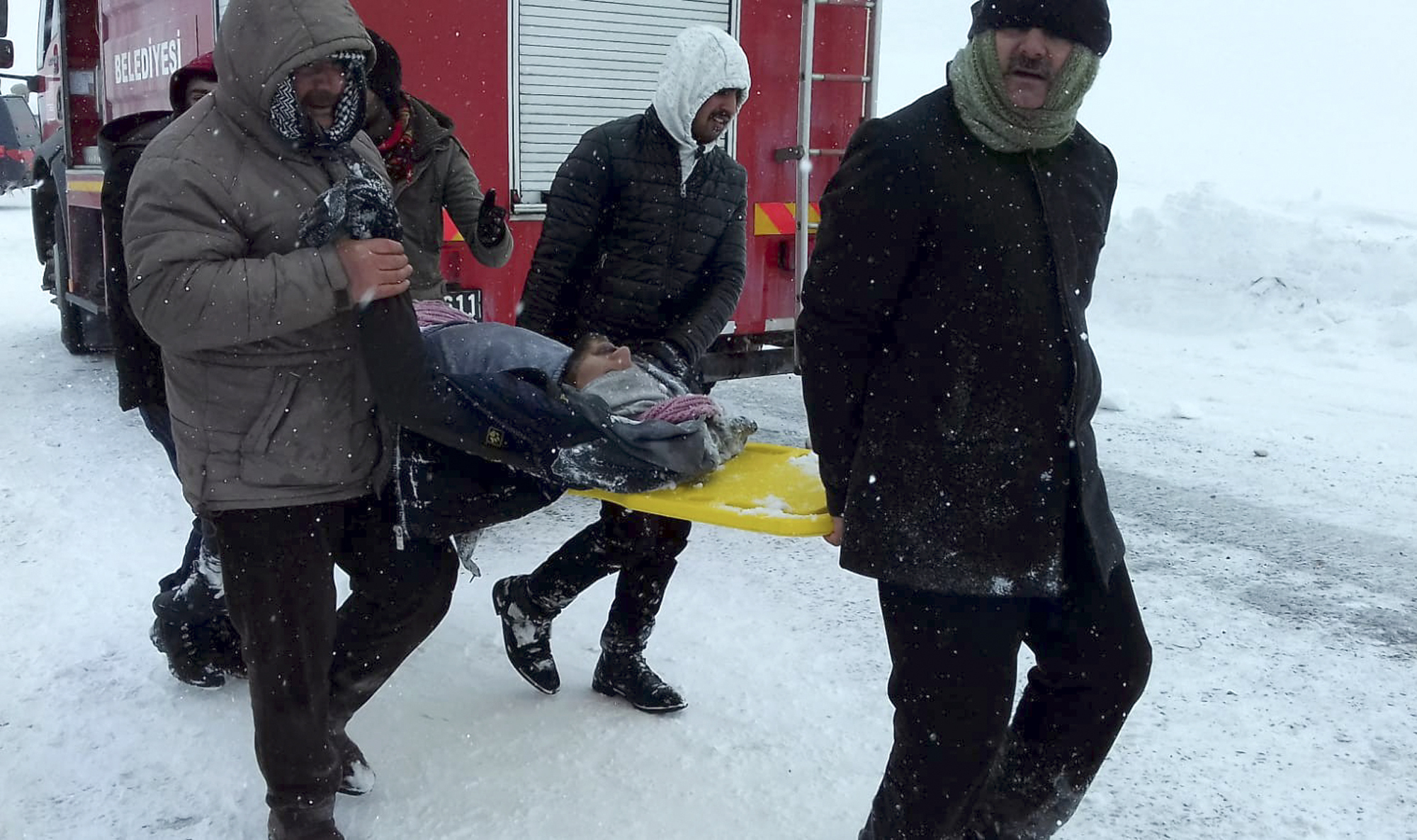 Emergency service members carry a casualty from an avalanche near the town of Bahcesehir, in Van province, eastern Turkey on Feb. 5, 2020.