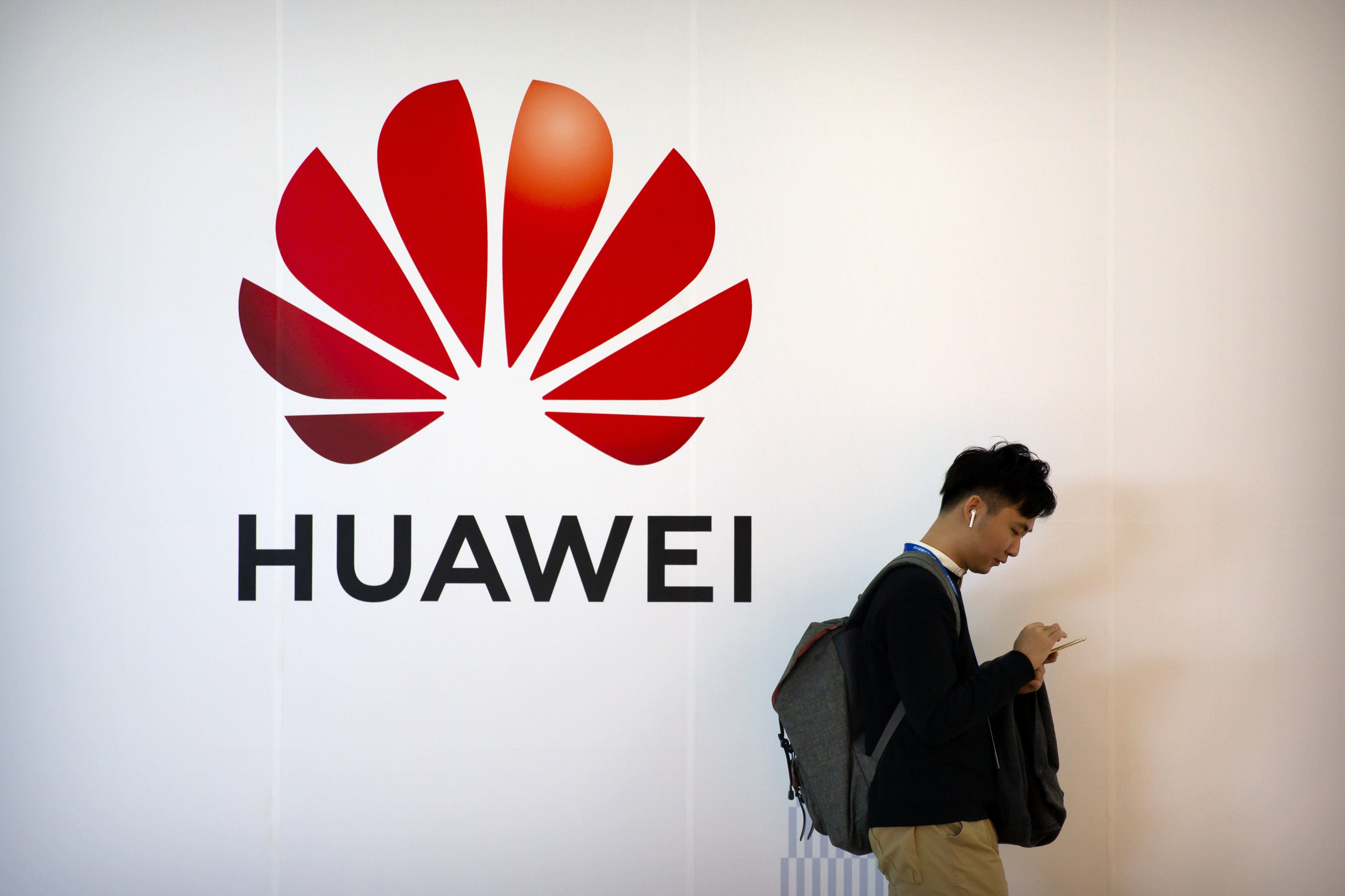 A man uses his smartphone as he stands near a billboard for Chinese technology firm Huawei at the PT Expo in Beijing on Oct. 31, 2019.