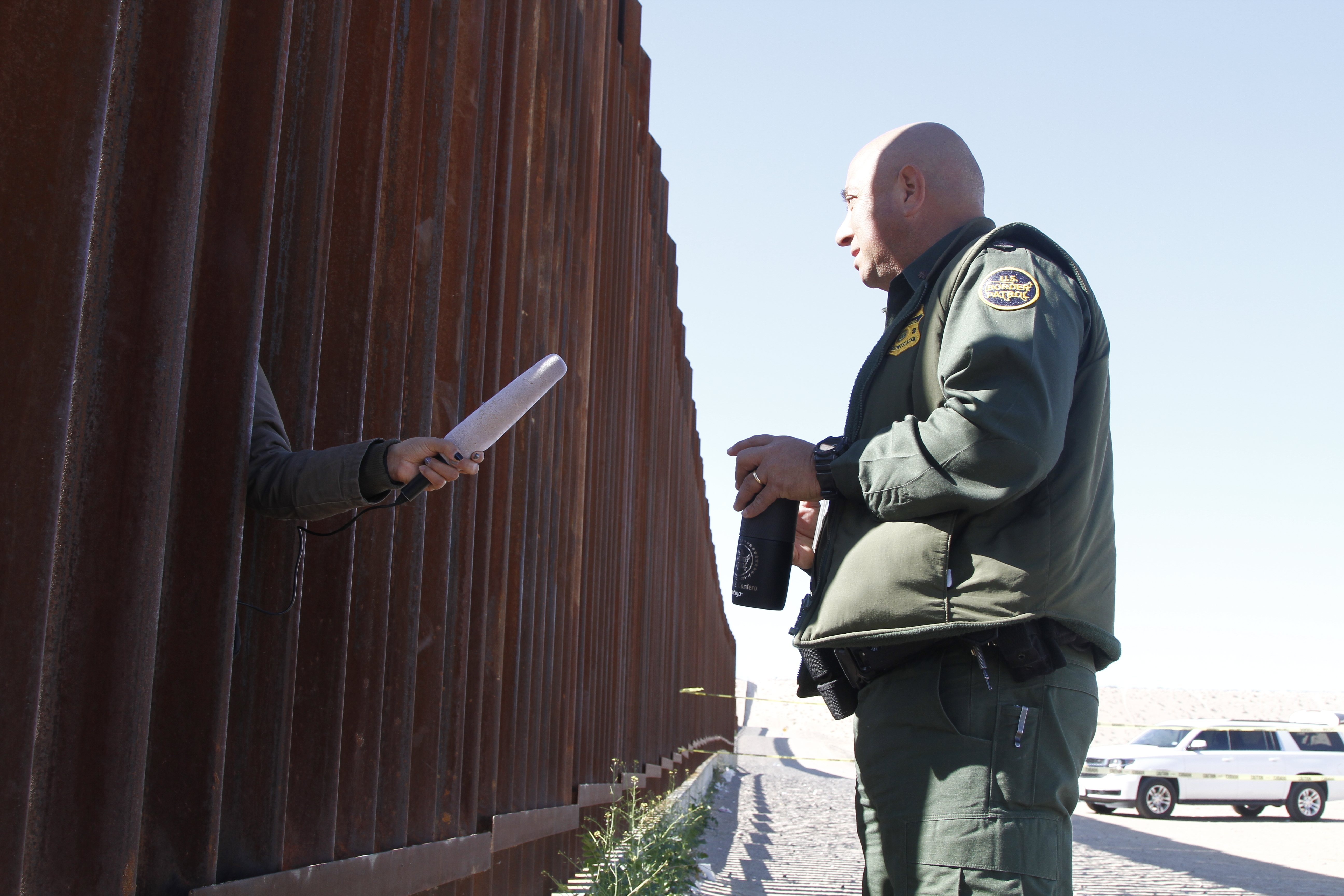 A journalist in Anapara, Mexico, sticks her microphone through a through a border fence to interview a Border Patrol agent following a training exercise on Friday, Jan. 31, 2020, in Sunland Park, New Mexico. Journalists in Mexico filmed the use-of-force exercises through gaps in the bollard-style wall.