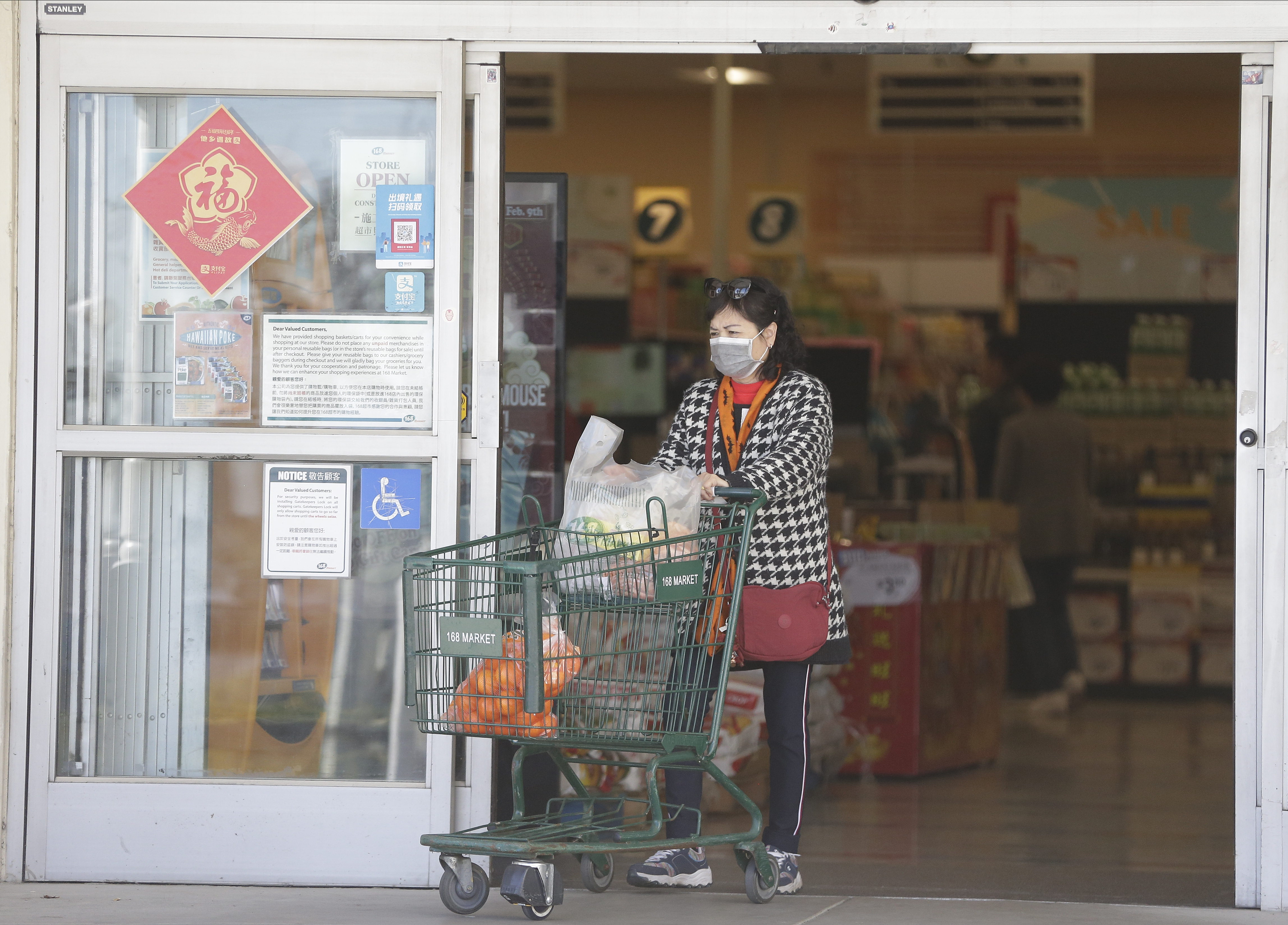 A customer wears a face mask as she shops at the 168 Market in Alhambra, Calif., on Jan. 31, 2020.