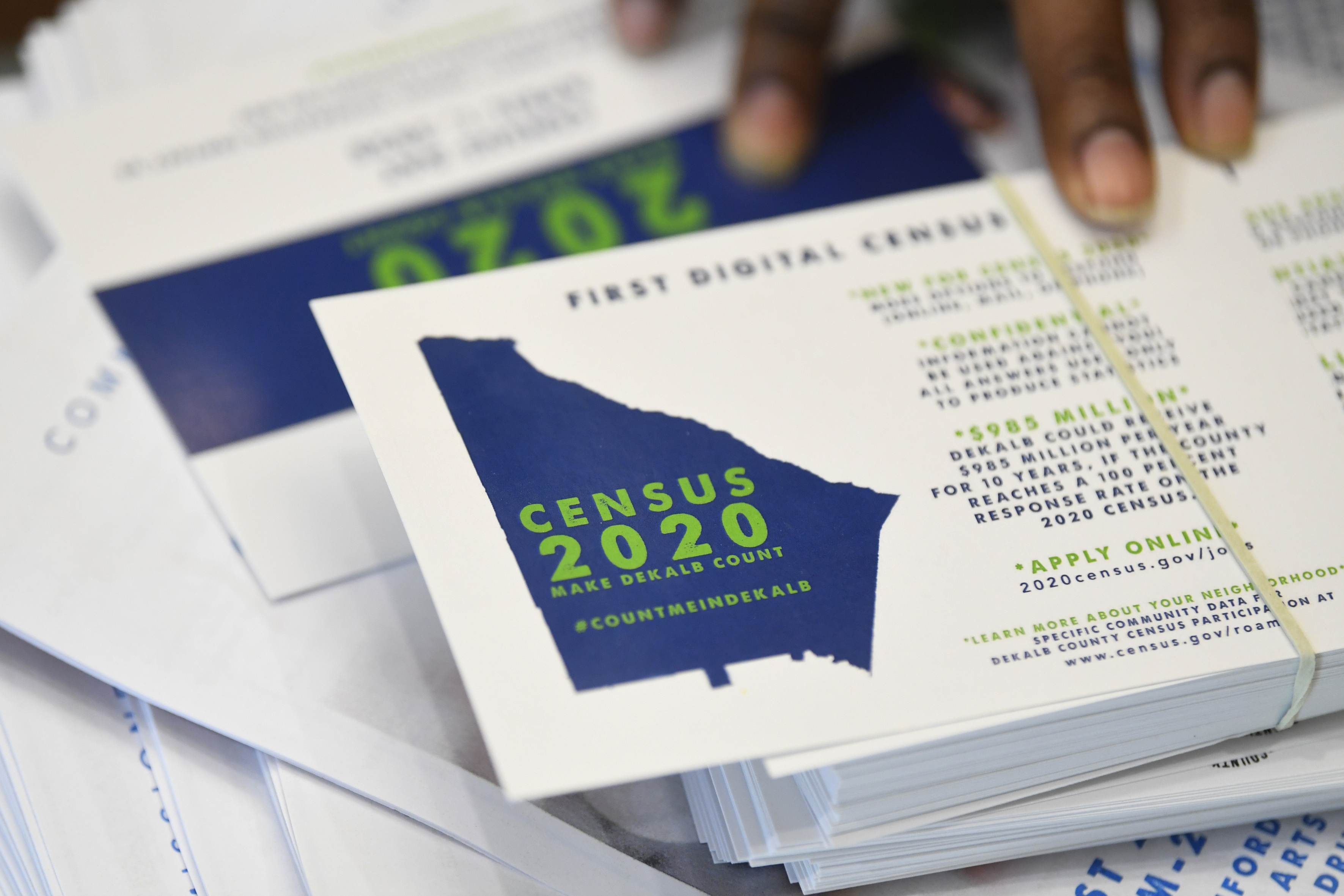 A worker gets ready to pass out instructions on how to fill out the 2020 census during a town hall meeting in Lithonia, Ga on Aug. 13, 2019.