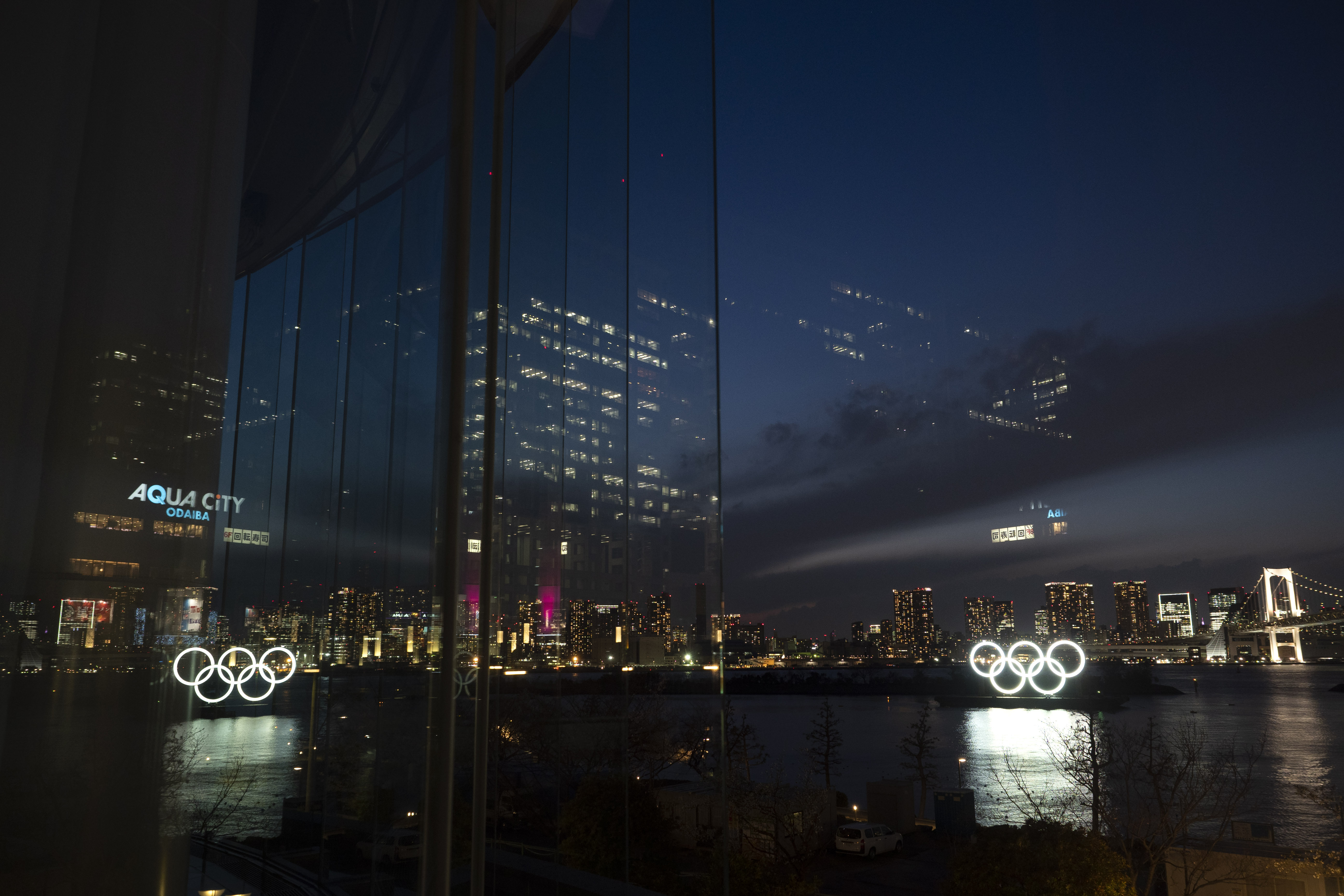 The Olympic rings are reflected in the glass wall of a wedding chapel in the Odaiba section of Tokyo, on March 23, 2020.
