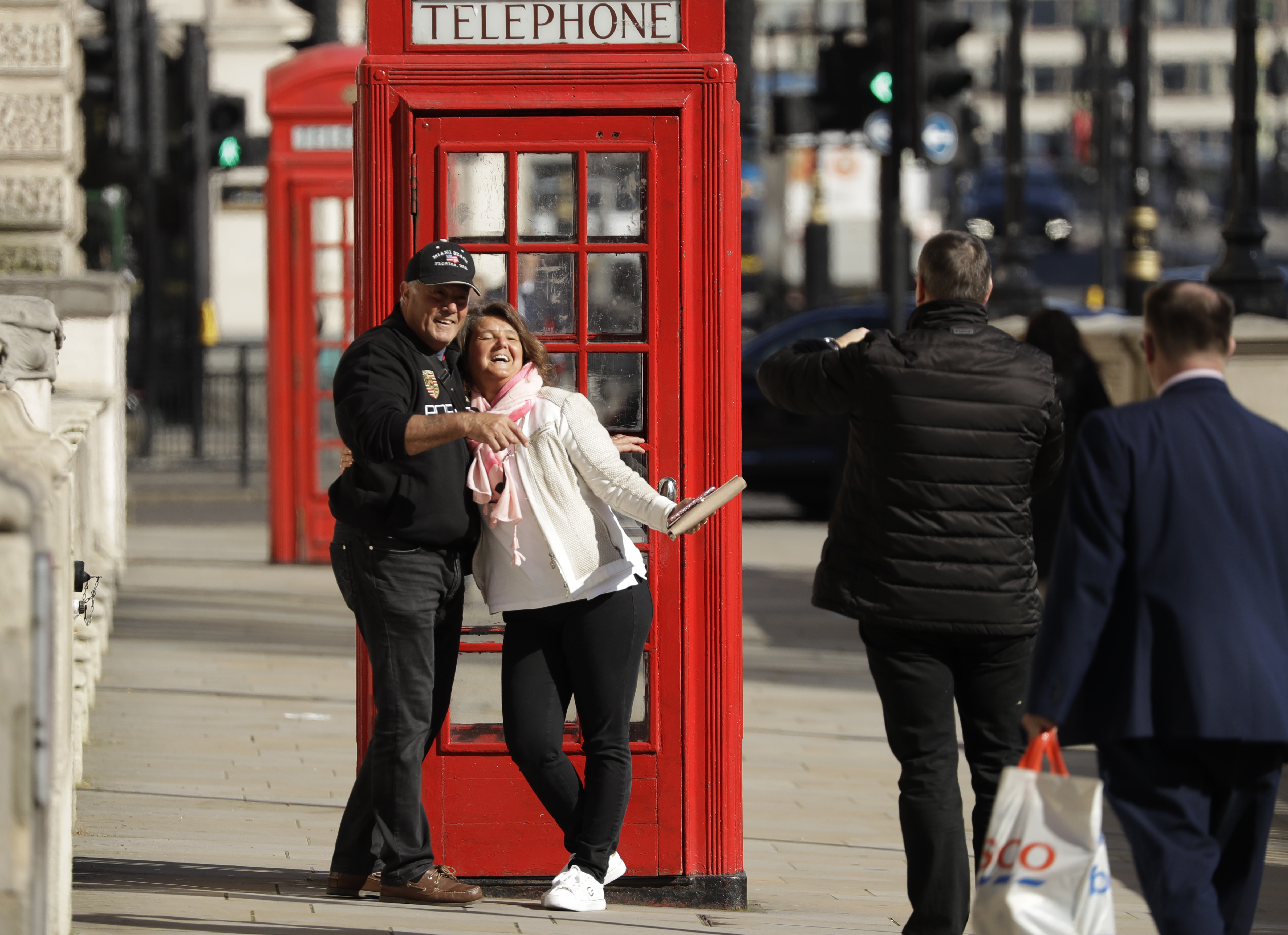 Two tourist have their photo taken next to a traditional red telephone box in Westminster, London, on March 23, 2020.