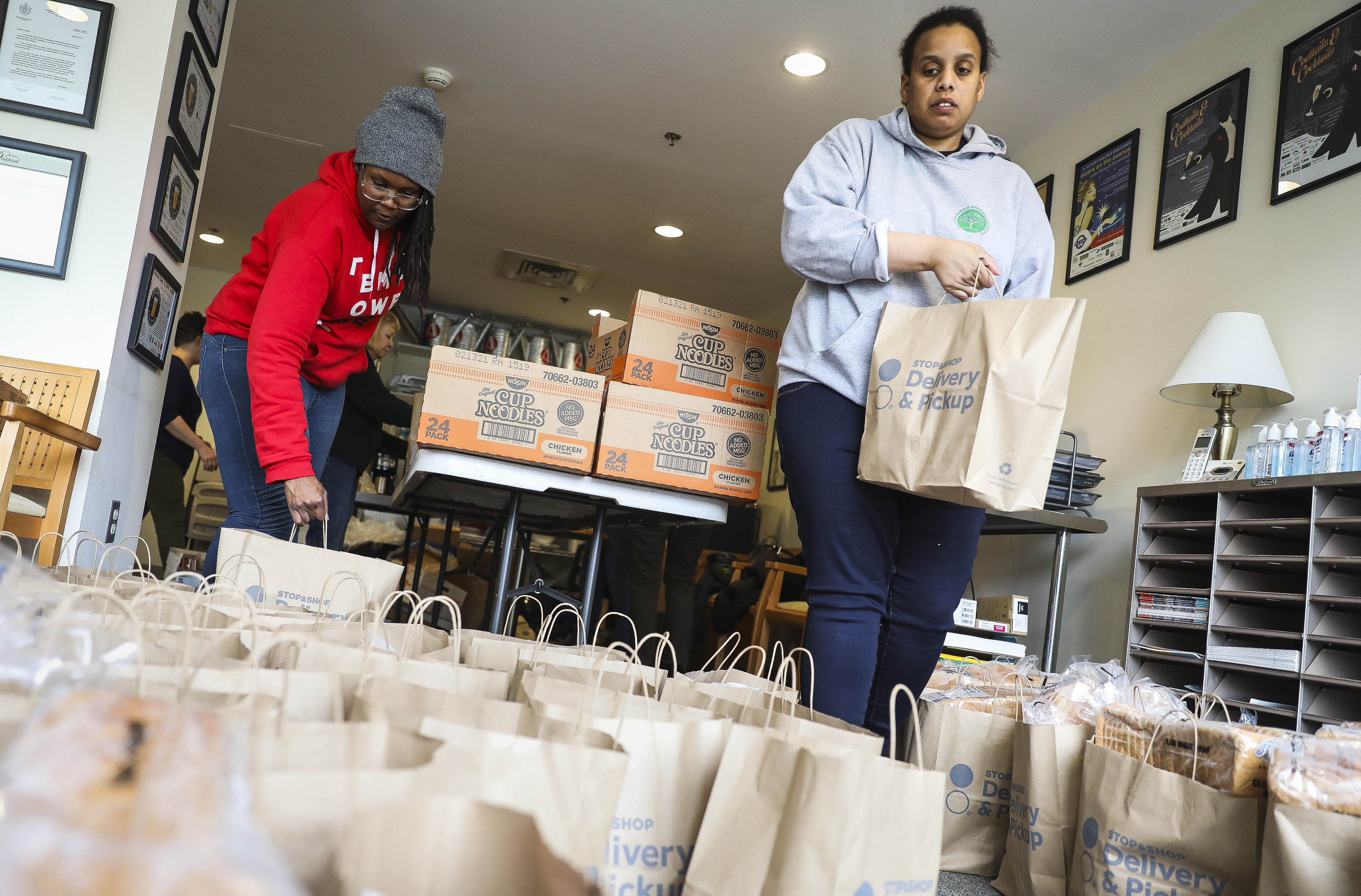 Joy Gary, left, and Yvonne Pope help bag donated food for students and families who may need it if the Boston Public Schools shut down, on March 11, 2020.