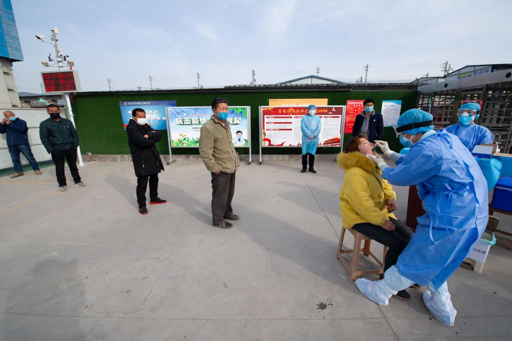 A medical worker wearing a protective suit collects sample from a migrant worker for a nucleic acid test for the COVID-19 coronavirus at a construction site amid the coronavirus outbreak on March 13, 2020 in Taiyuan, Shanxi Province of China.