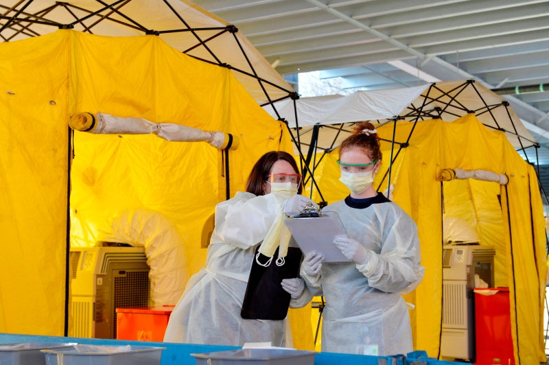Hospital clinicians work to test patients for the coronavirus, Covid-19 at Newton-Wellesley Hospital in Newton, Massachusetts on March 18, 2020, as the hospital has set up three tents in the parking garage where patients who have been pre-screened can show up for testing.