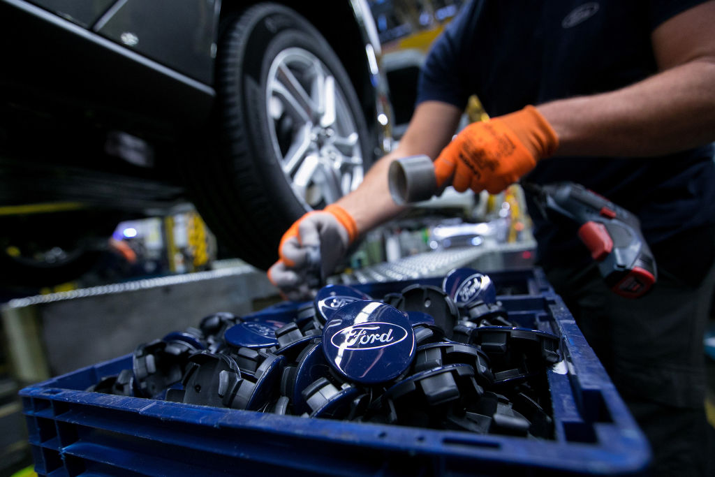 A worker fits wheel hub badges on the Ford Focus automobile assembly line inside the Ford Motor Co. factory in Saarlouis, Germany, on Wednesday, Sept. 25, 2019.