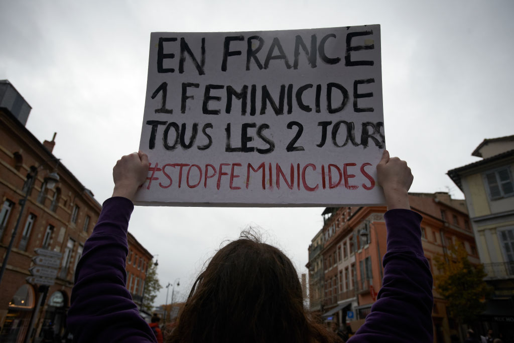 A woman holds a placard 'In France a femenicide every two days'.