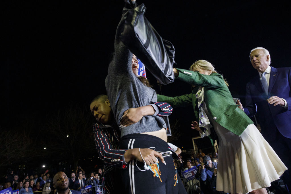 Former Vice President Joe Biden watches as his wife Jill Biden and his senior adviser Symone Sanders block a protester from arriving on stage during a primary night rally in the Baldwin Hills neighborhood of Los Angeles, Calif., on Tuesday, March 3, 2020.