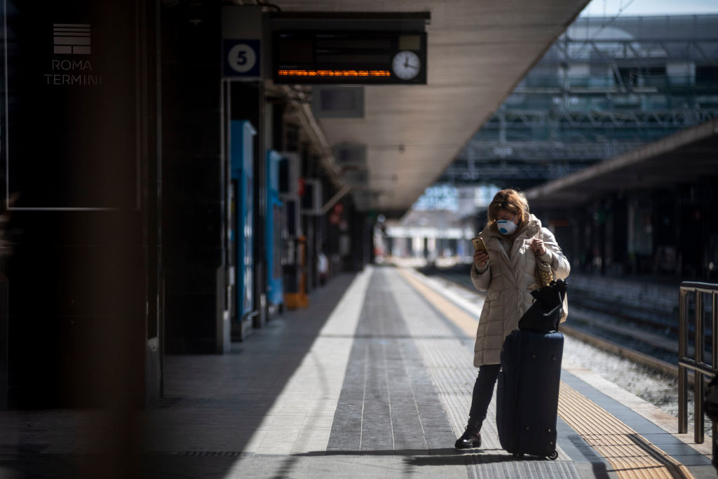 A passenger wearing face masks waits at the Termini Central Station during the Coronavirus emergency, on March 9, 2020 in Rome, Italy. Italian Prime Minister Giuseppe Conte announced the closure of the Italian region of Lombardy in an attempt to stop the ongoing coronavirus epidemic in the Italian country.