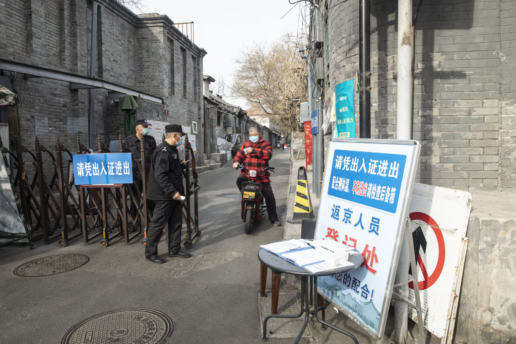 A motorcyclist wearing a protective mask shows his identification at a check point as he leaves a neighborhood in Beijing, China, on March 18, 2020.