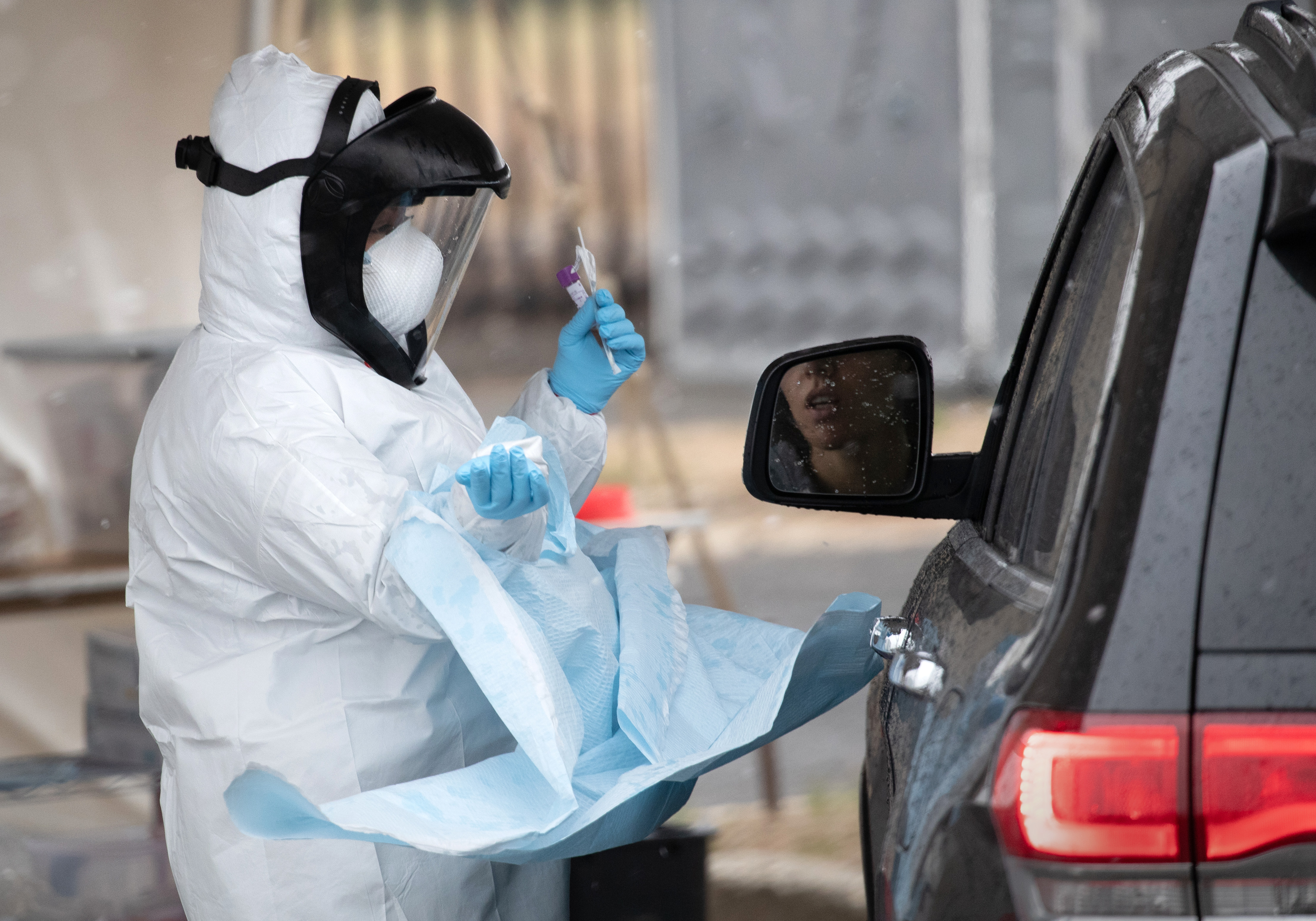 A nurse prepares to give a coronavirus swab test at a drive-thru testing station at Cummings Park on March 23, 2020 in Stamford, Connecticut