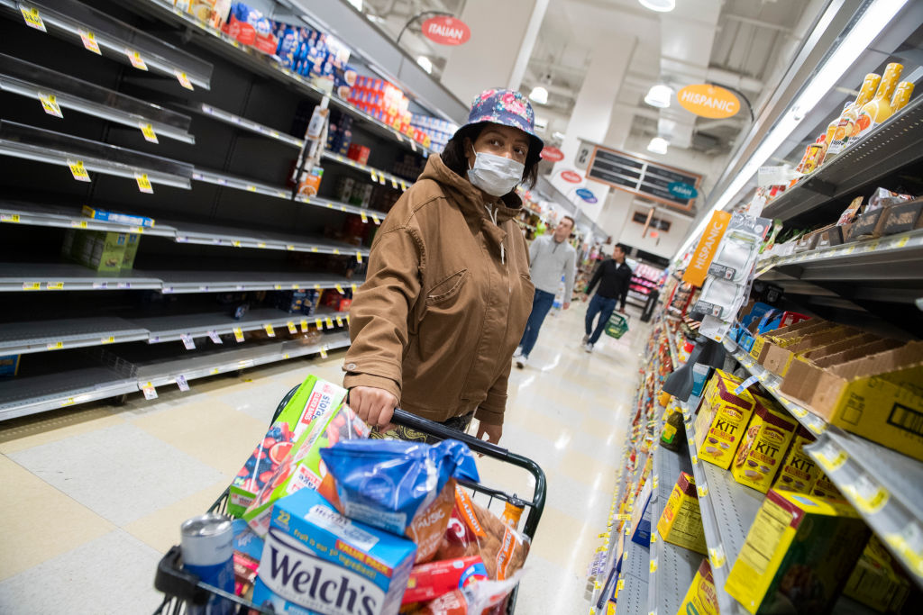 A shopper wears a face mask due to the coronavirus outbreak while browsing an aisle in the Harris Teeter on First Street, NE, on Monday, March 23.