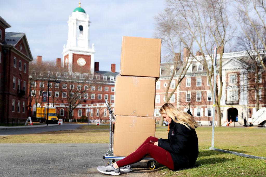 Harvard Sophomore Jordan Di Verniero, 19, sits with her belongings in front of Eliot House before returning home to Ormond Beach, Florida, for the rest of the semester on March 12 in Cambridge, Massachusetts.