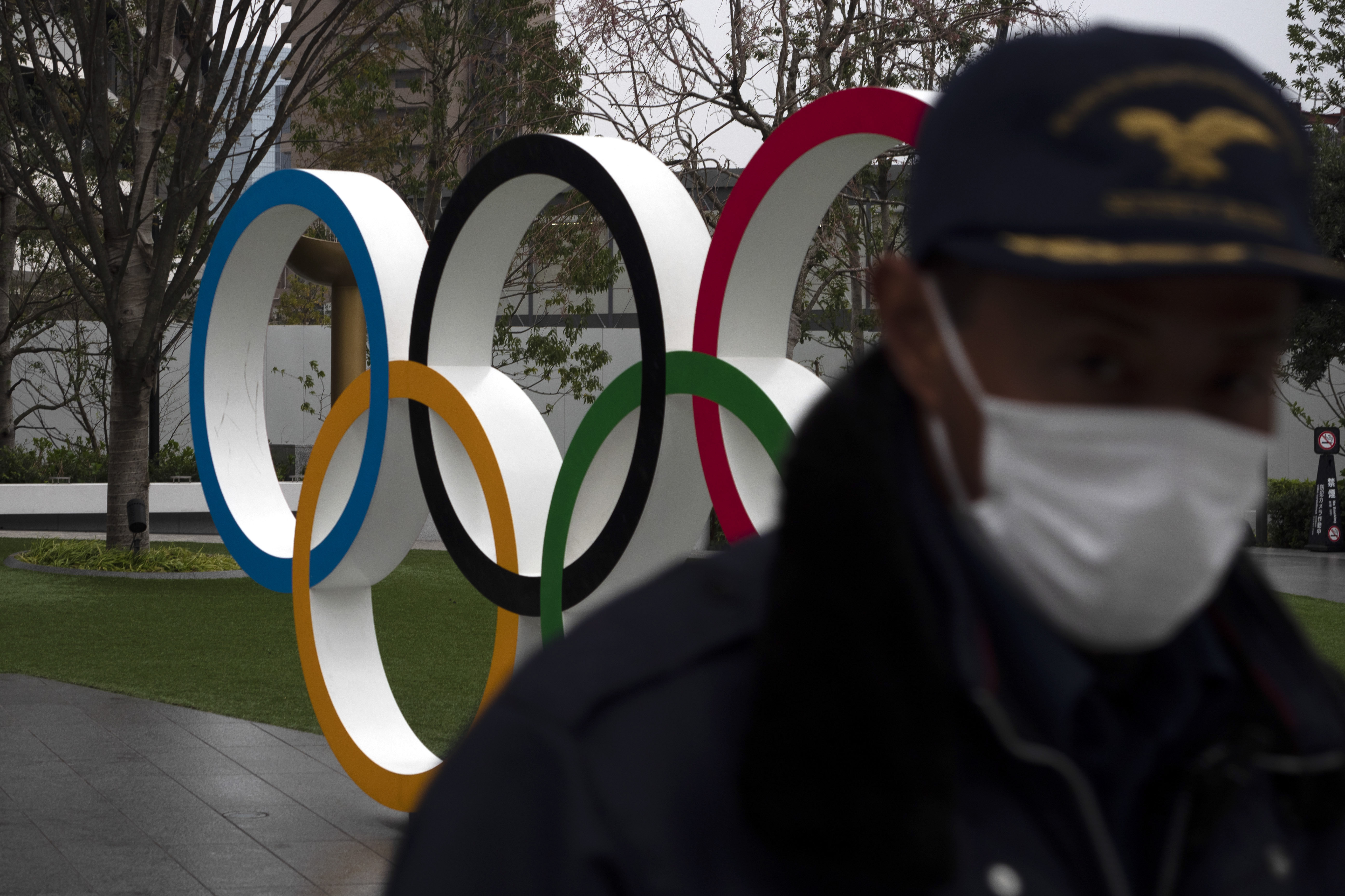 A security guard walks past the Olympic rings near the New National Stadium in Tokyo, Monday, March 23, 2020. The IOC will take up to four weeks to consider postponing the Tokyo Olympics amid mounting criticism of its handling of the coronavirus crisis that now includes a call for delay from the leader of track and field, the biggest sport at the games.