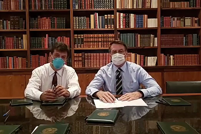 In this handout photo released by Brazil's Presidential Press Office, Brazilian Health Minister Luiz Henrique Mandetta, left, and President Jair Bolsonaro, wear masks as they speak about the new coronavirus during a Facebook Live transmission, in Brasilia, Brazil on March 12, 2020.