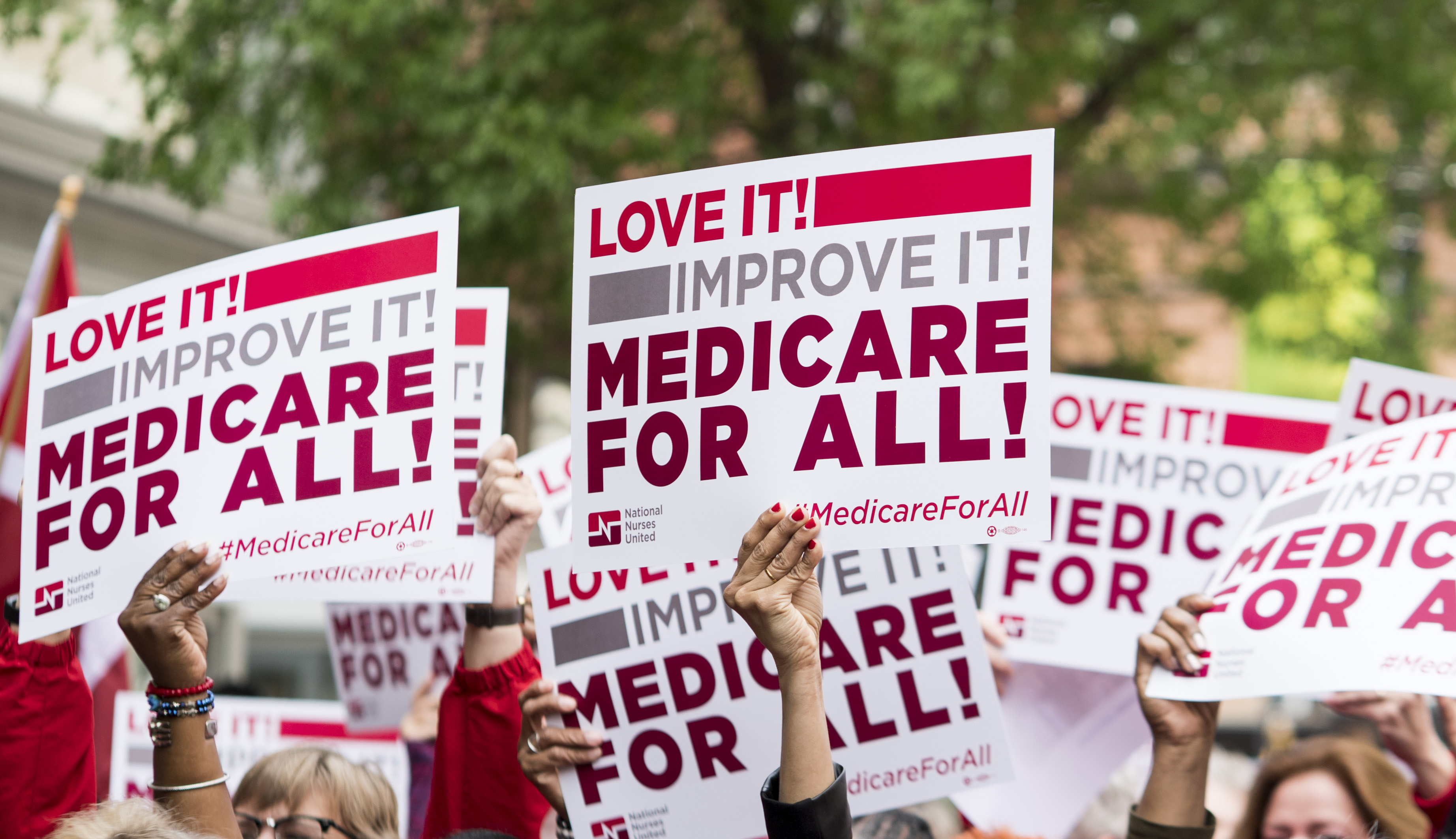 Members of National Nurses United union members wave  Medicare for All  signs during  a rally in front of the Pharmaceutical Research and Manufacturers of America in Washington calling for  Medicare for All  on Monday, April 29, 2019.