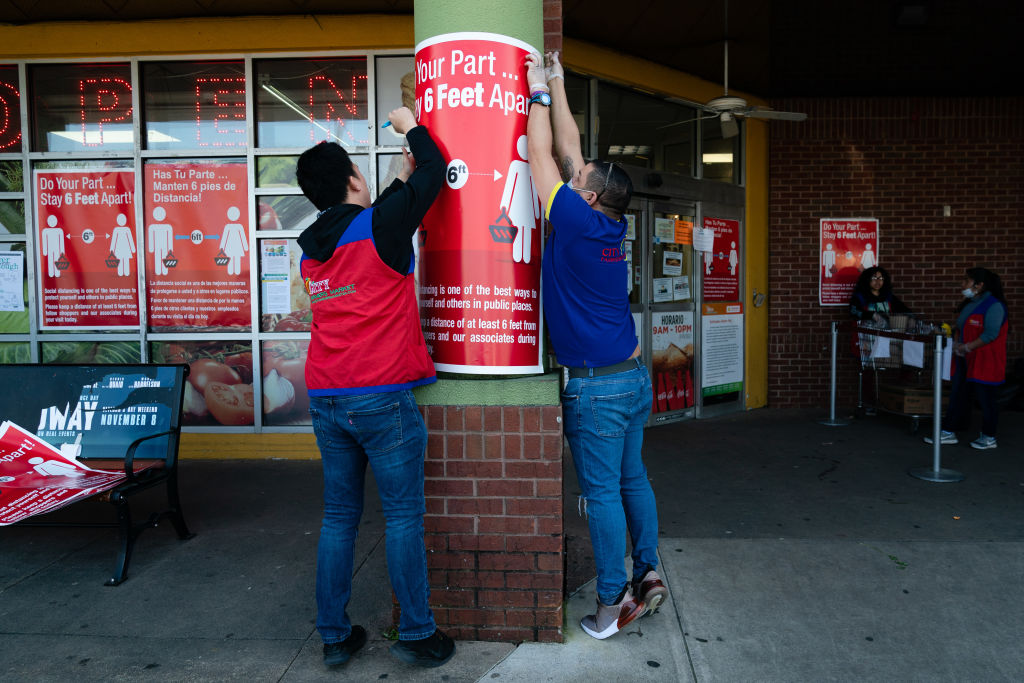 Workers place signs notifying customers of social distancing guidelines outside a City Farmers Market supermarket in Duluth, Georgia, on March 26, 2020.