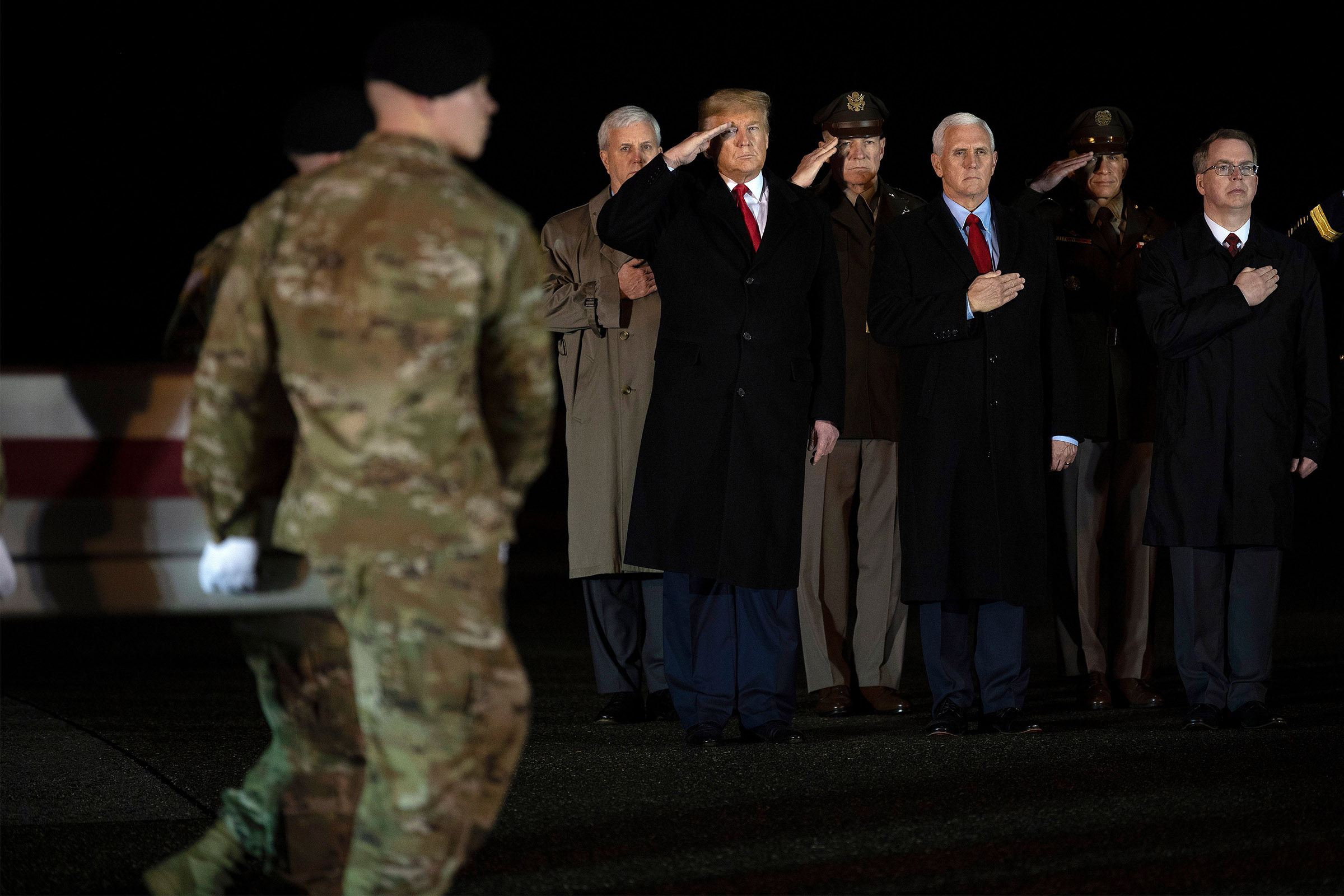 US President Donald Trump (L) and Vice President Mike Pence (C) observe the dignified transfer of two US soldiers killed in Afghanistan, at Dover Air Force Base in Dover, Delaware, on Feb. 10, 2020.
