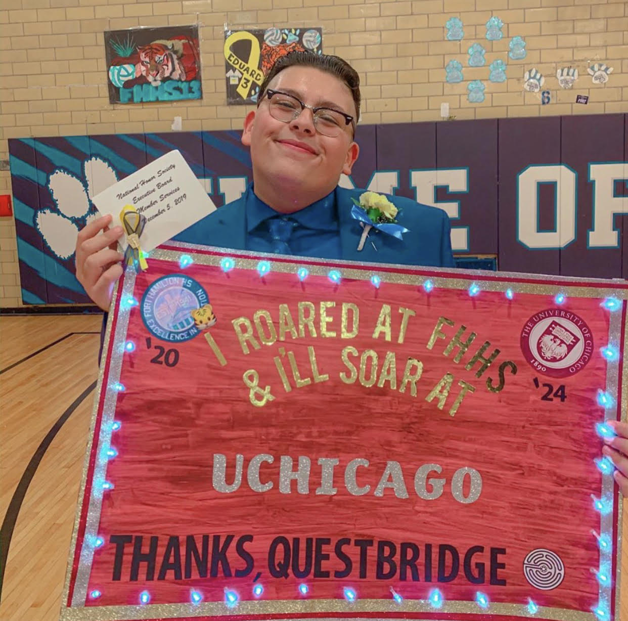 17-year-old Youssef Hasweh holds up a thank-you poster he made for Questbridge, which matches low-income students to scholarships at top colleges. Hasweh applied to the University of Chicago through the non-profit and will begin classes at the school in the fall.