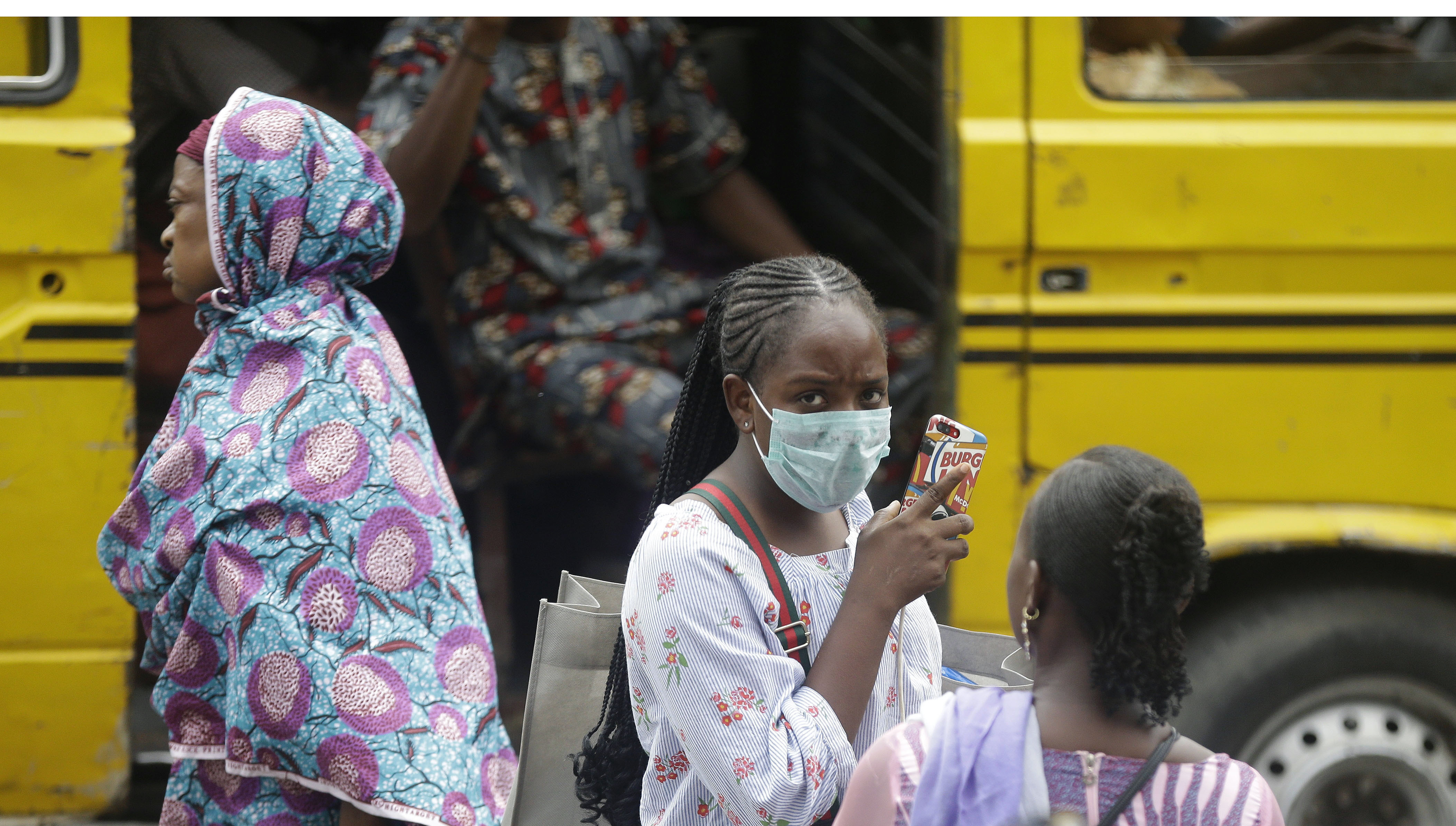 A woman wearing a face mask walks nearby the Central Mosque in Lagos, Nigeria on March 20, 2020.