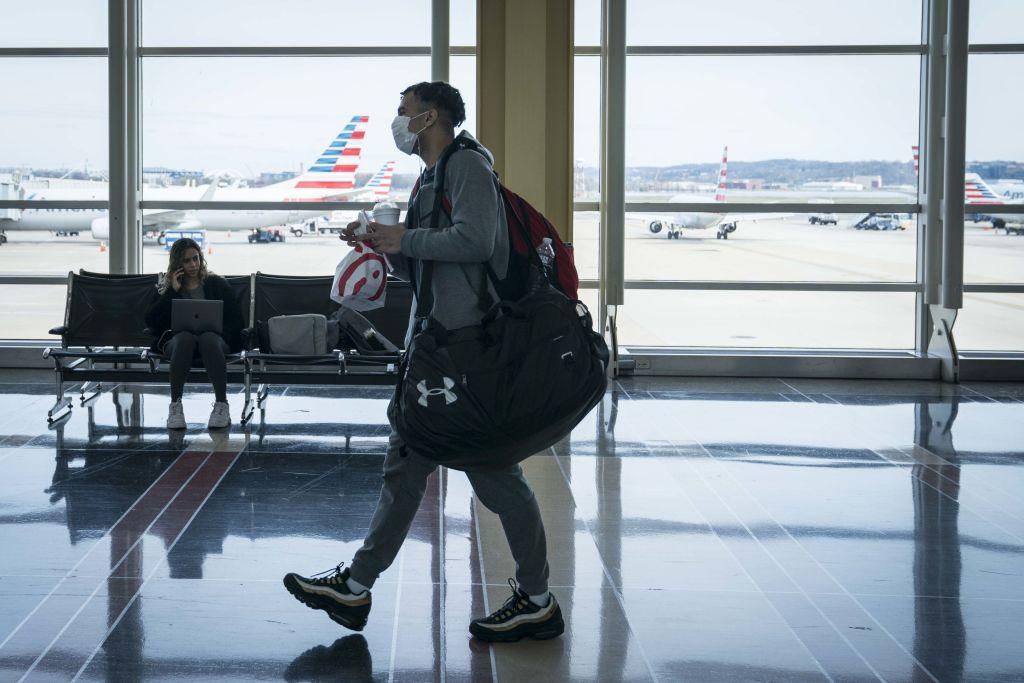 A traveler wears a face mask at Ronald Reagan National Airport in Arlington, Va., on Mar. 16, 2020.