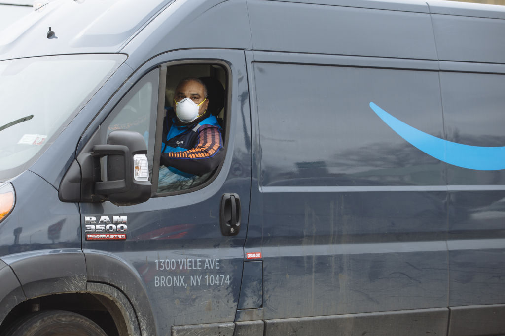 A driver wears a protective mask while traveling in an Amazon.com Inc. delivery truck in New Rochelle, New York, U.S., on Thursday, March 12, 2020.