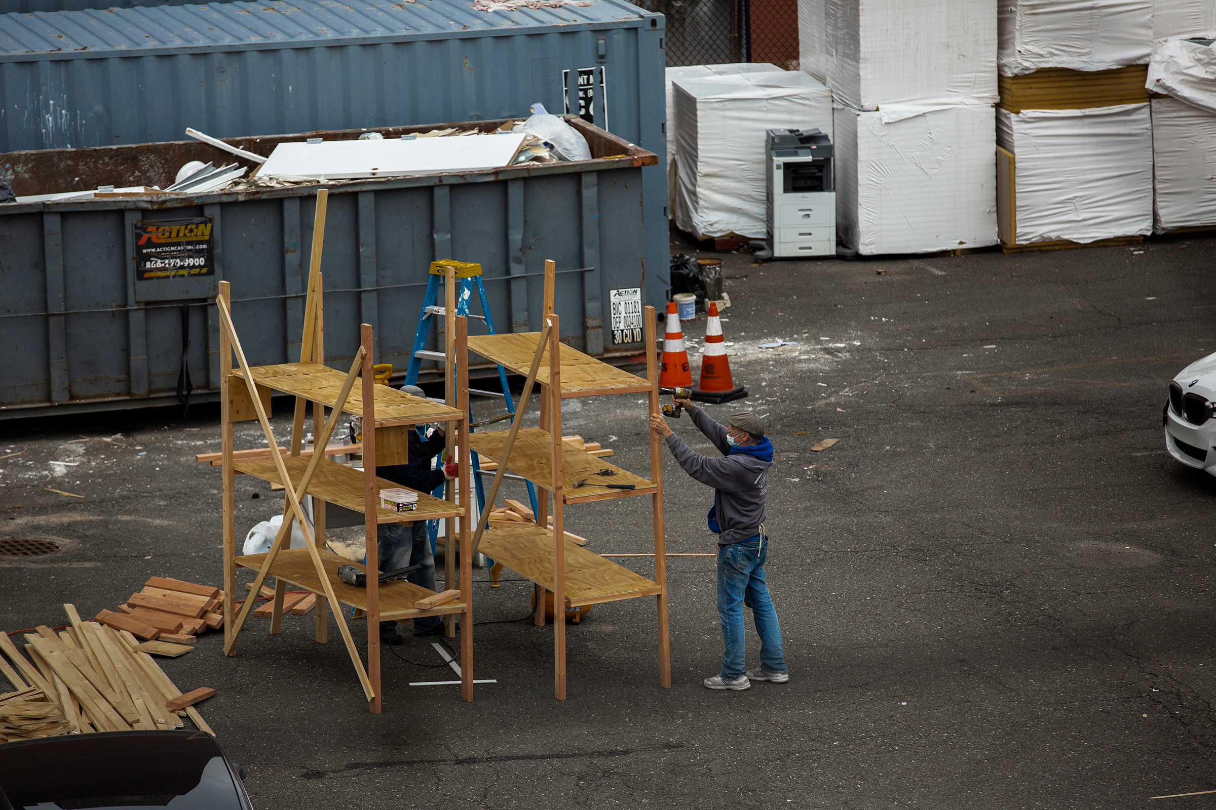 Workers build shelves for a makeshift morgue outside Wyckoff Heights Medical Center in Brooklyn, New York, on March 30, as seen from an apartment building across the street.