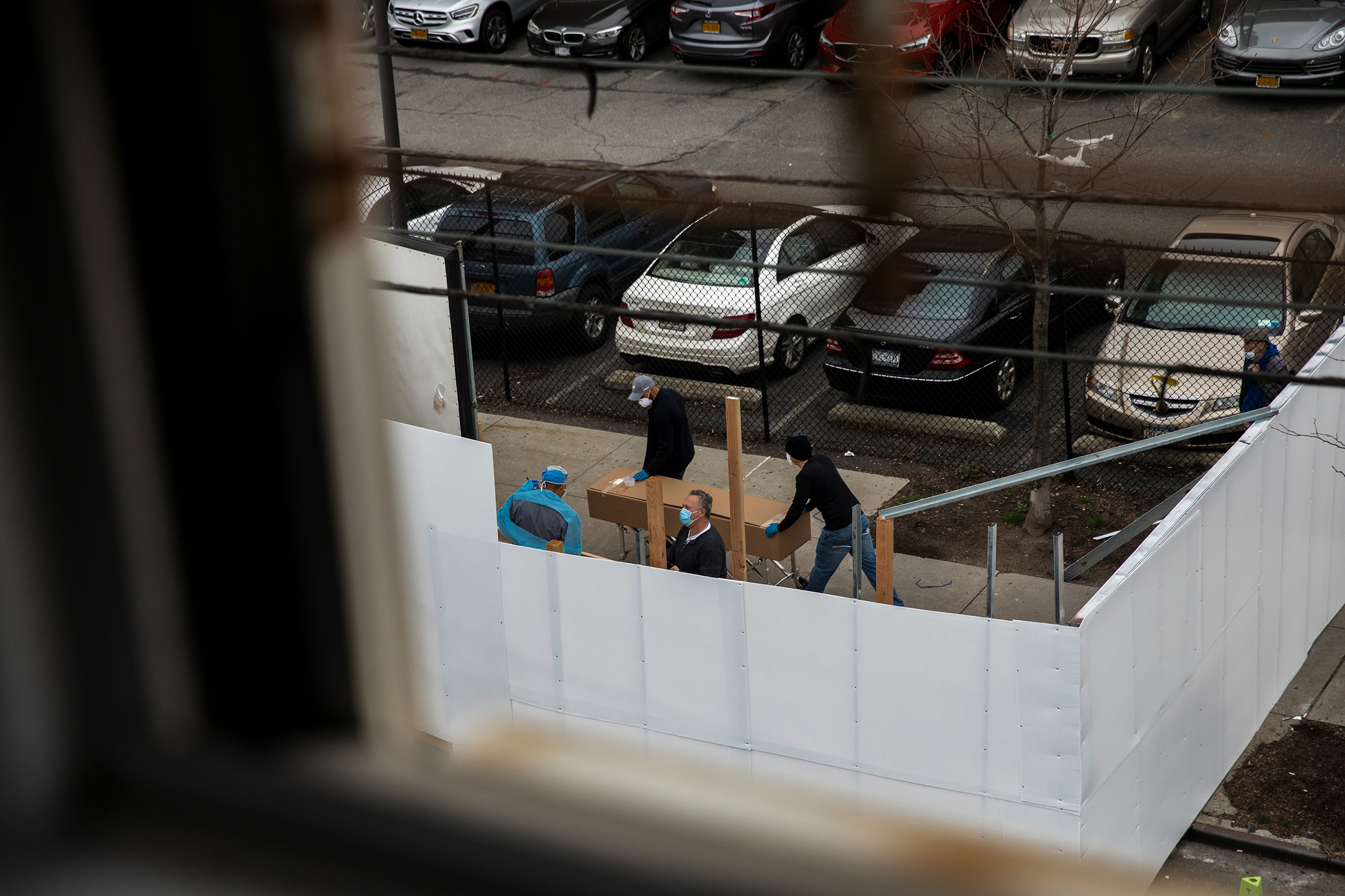 Workers transport a casket-sized box near the morgue set up outside Wyckoff Heights Medical Center in Brooklyn on March 30.